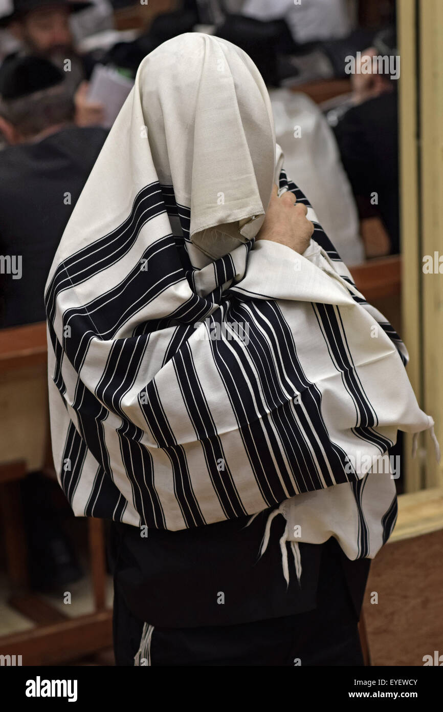 An orthodox Jewish man blesses and puts on his prayer shawl at morning services in Brooklyn, New York - Stock Image