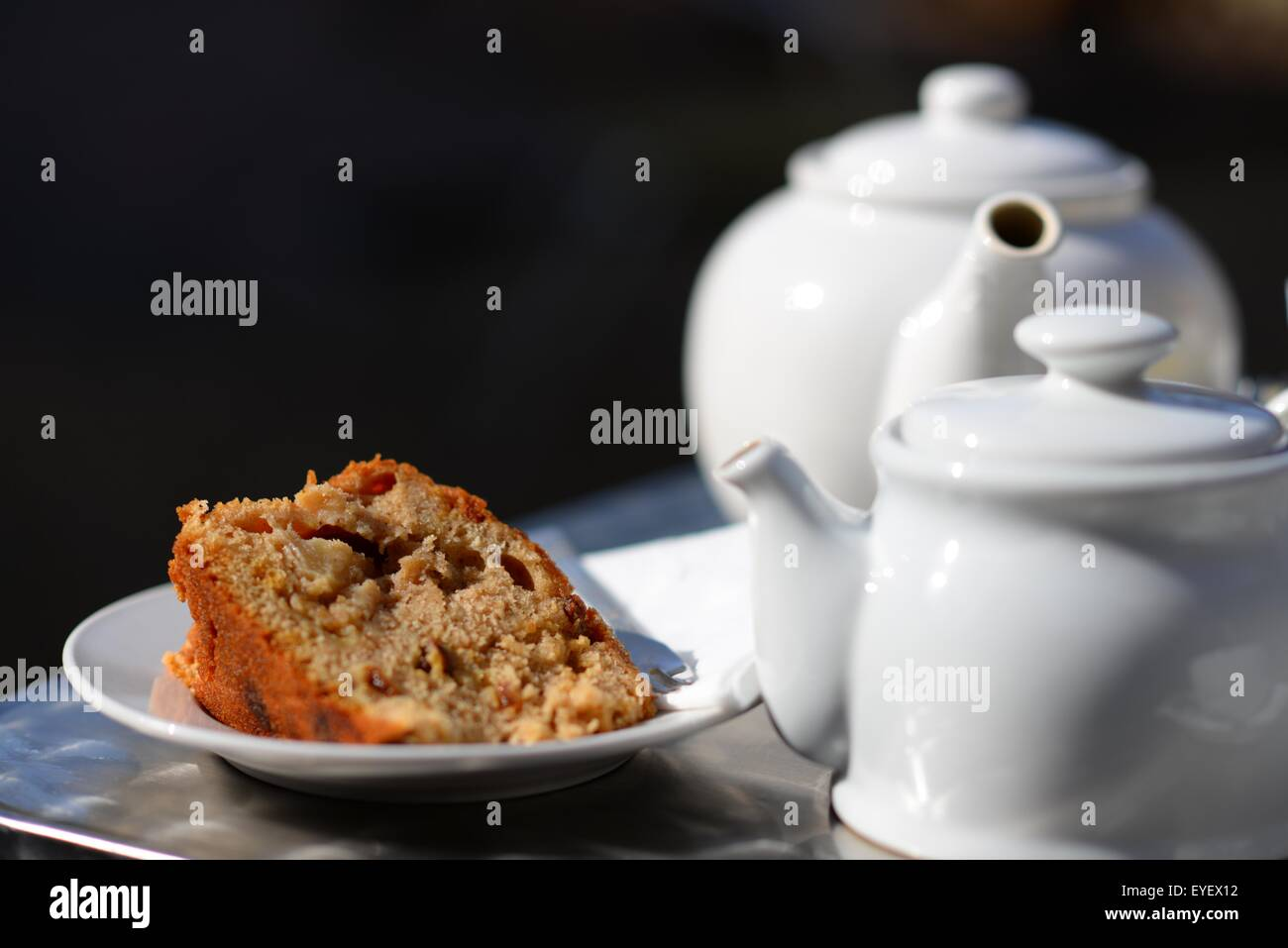 English afternoon tea for two in the garden with a large slice of walnut cake. - Stock Image