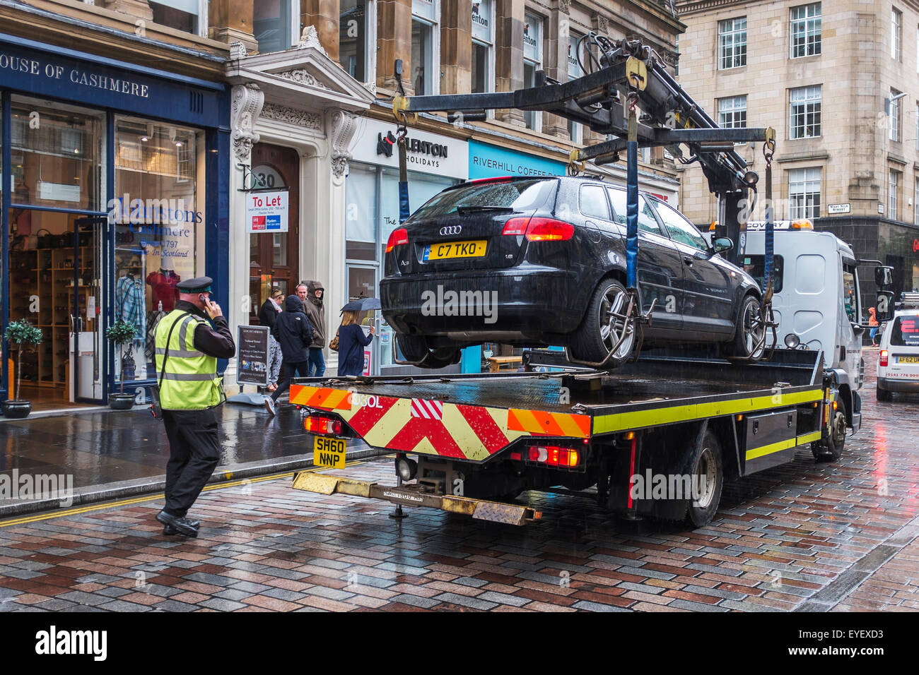 Traffic warden authorising the removal of a car parked illegally, Glasgow, Scotland, UK - Stock Image
