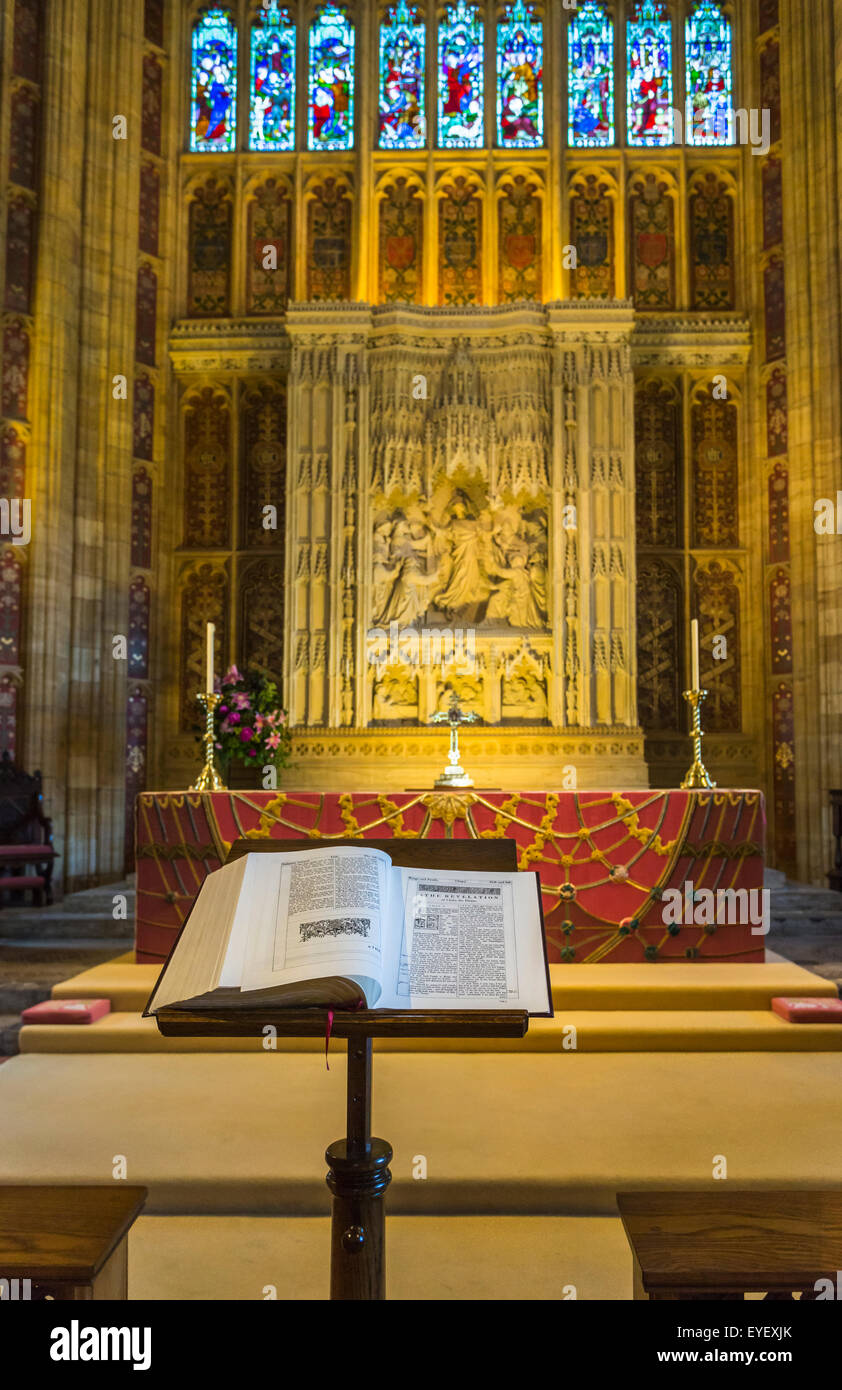The Holy Bible on a lectern open at the book of Revelation in front of the altar in Sherborne Abbey, Sherborne, - Stock Image