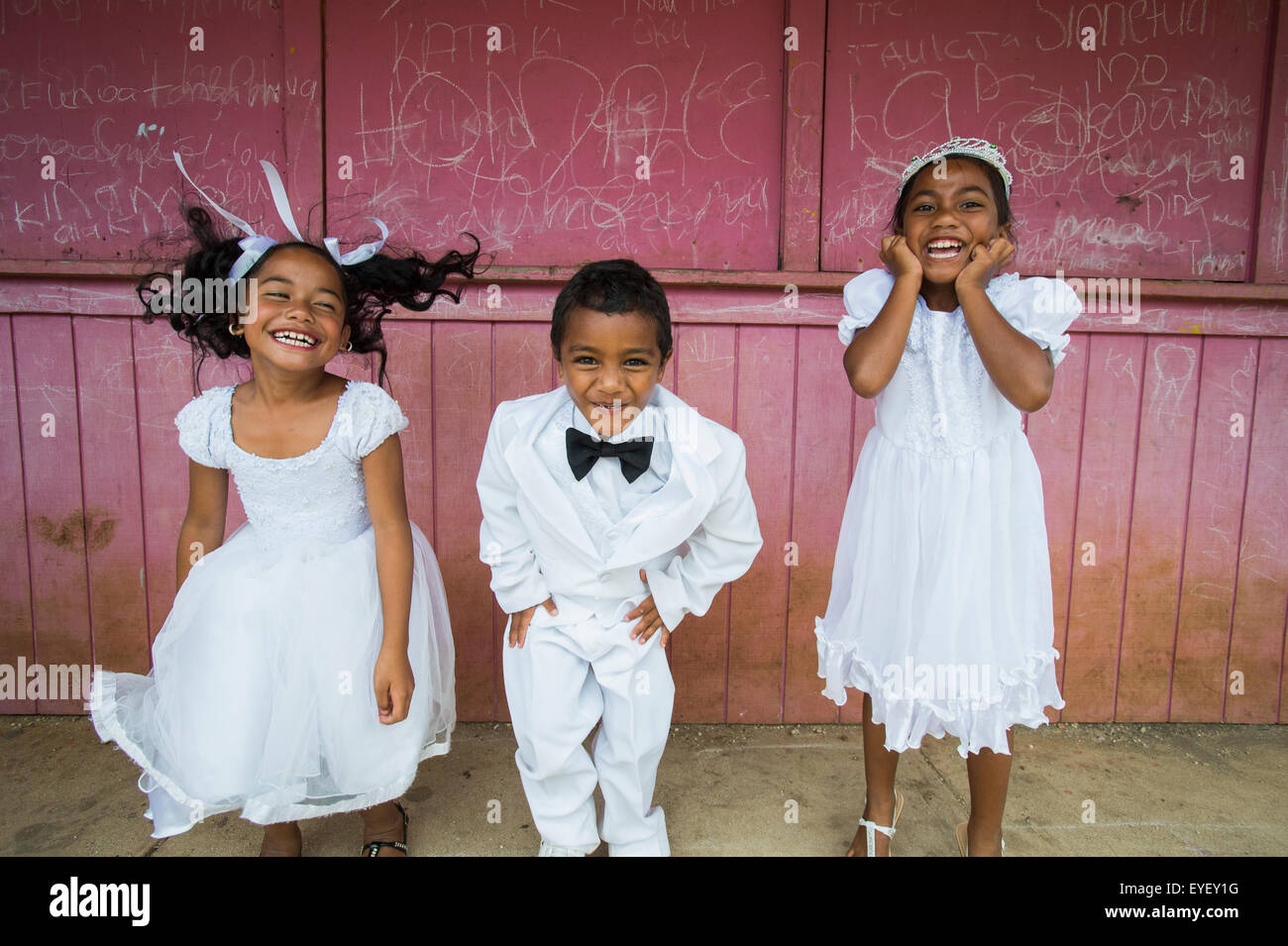 Children dressed in white formal wear against a red wall; Hapai Island, Tonga - Stock Image