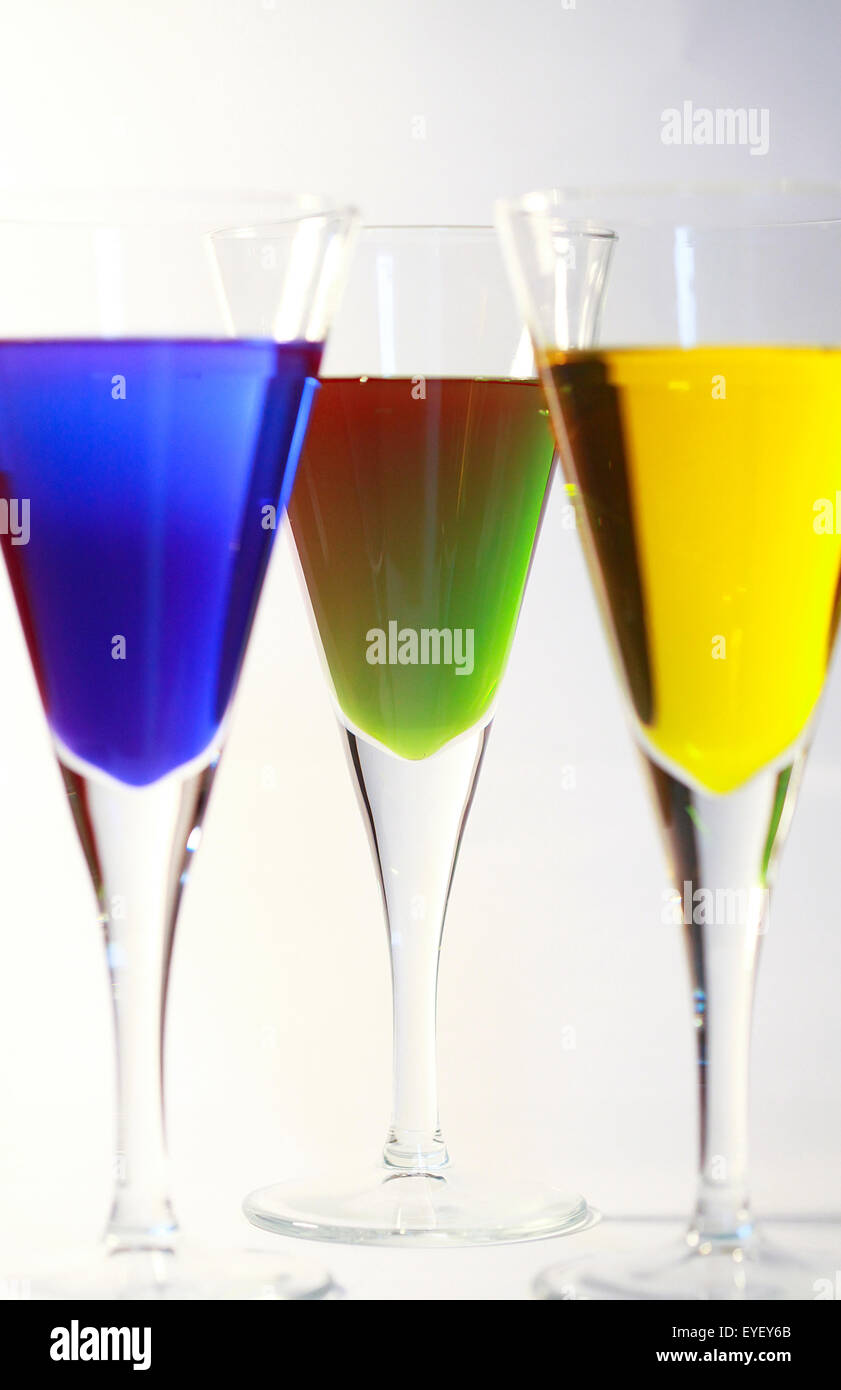 Three cocktails of bright colored alcohol against a white background - Stock Image