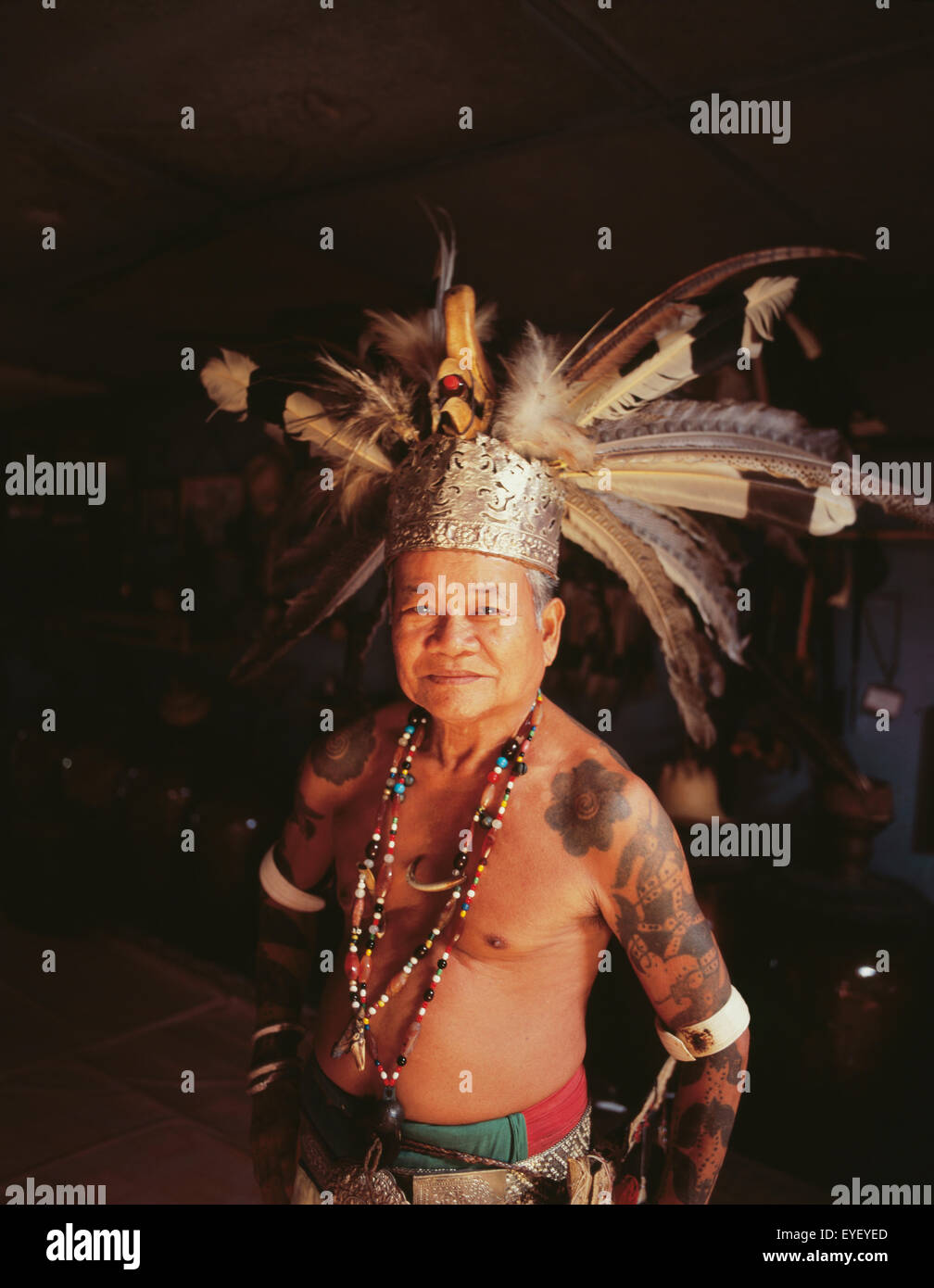Village chief standing in a Long House in traditional dress; Sarawak Stock Photo