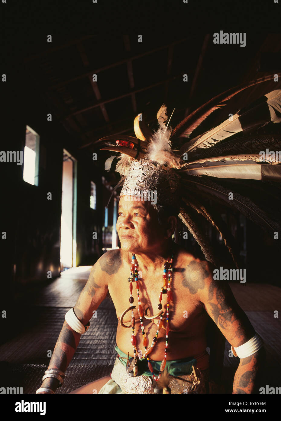 Village chief sitting in a Long House in traditional dress; Sarawak - Stock Image
