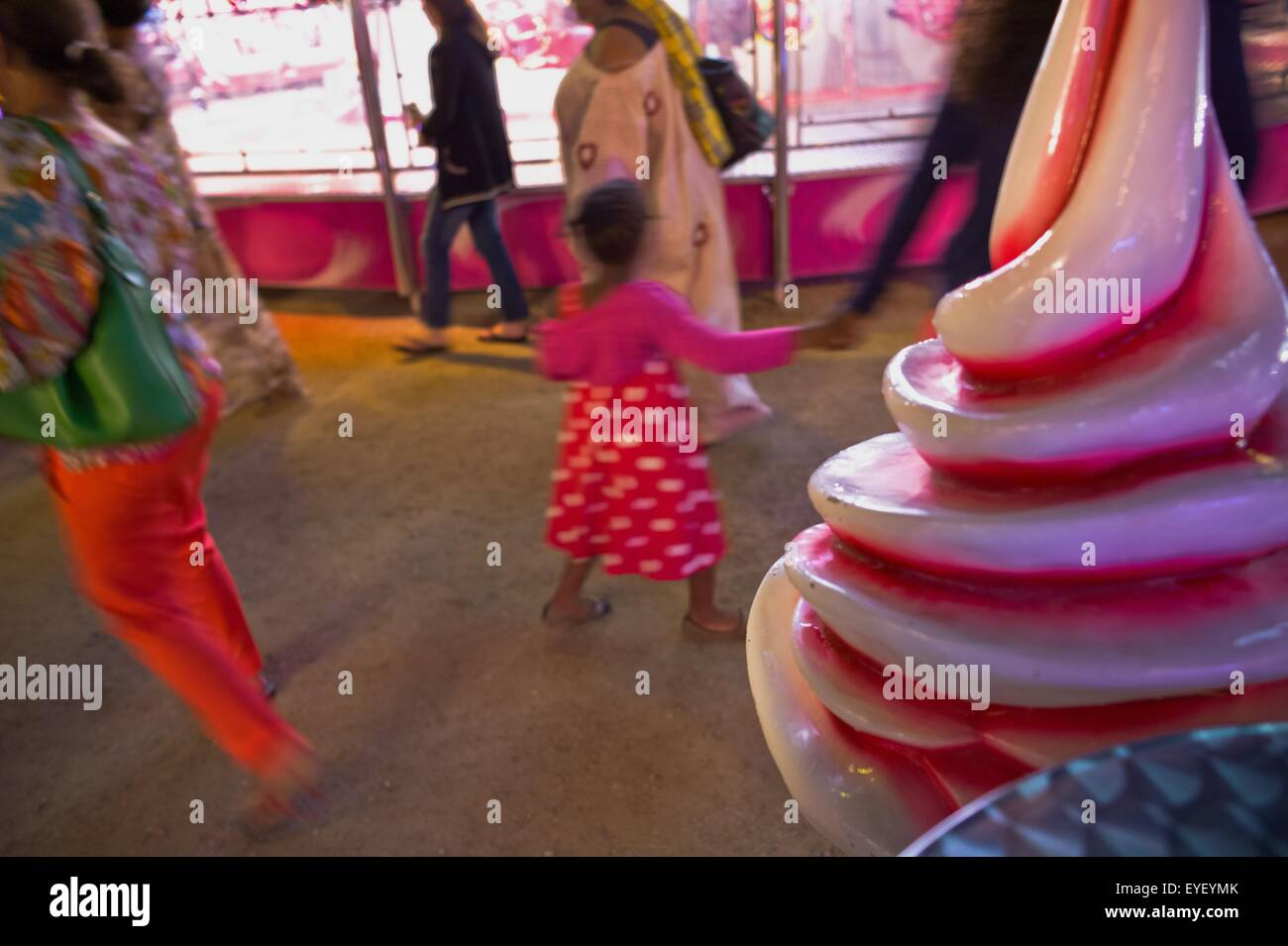 Scene of Saturday evening in the fun fair In a place steeped in history of France, every summer the Garden of the Tuileries welcomes about sixty fairground attractions for the enjoyment and the pleasure of the children and the parents. For several years t Stock Photo