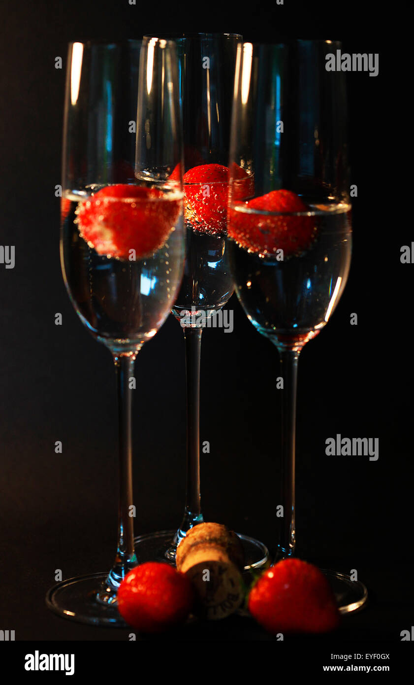 Three glasses of champagne cocktails against a black backdrop Stock Photo