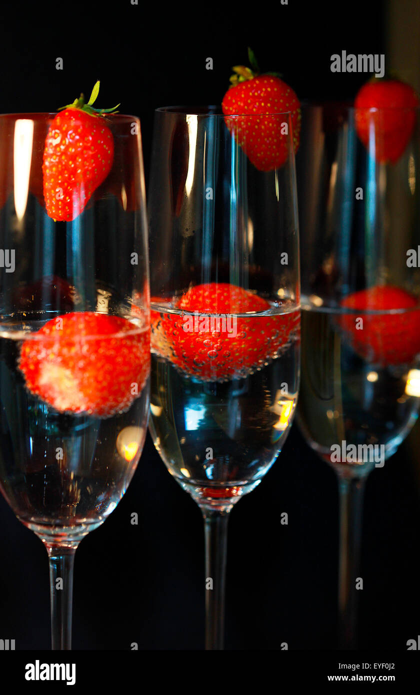 Three glasses of champagne cocktails against a black backdrop - Stock Image