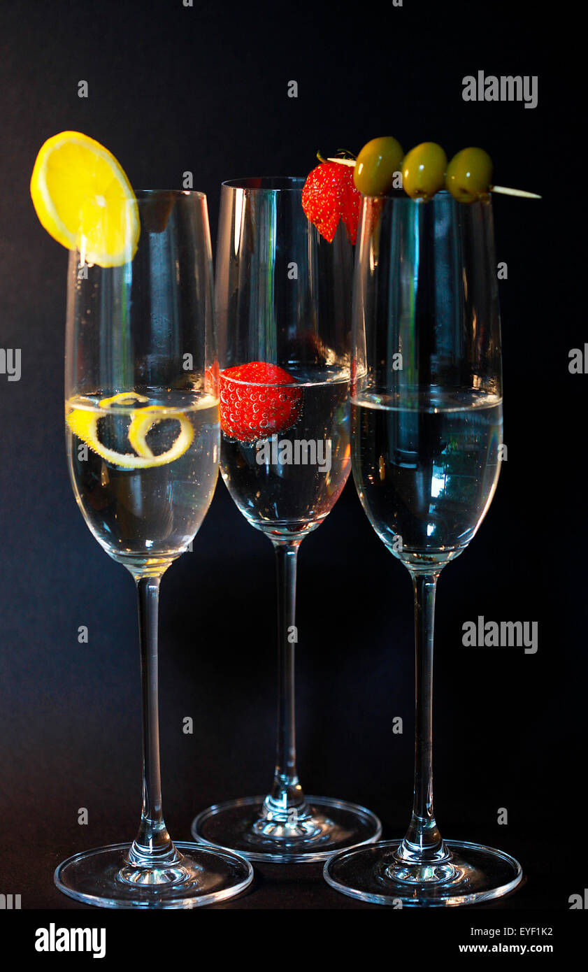 Three assorted cocktails with garnish against a black backdrop - Stock Image