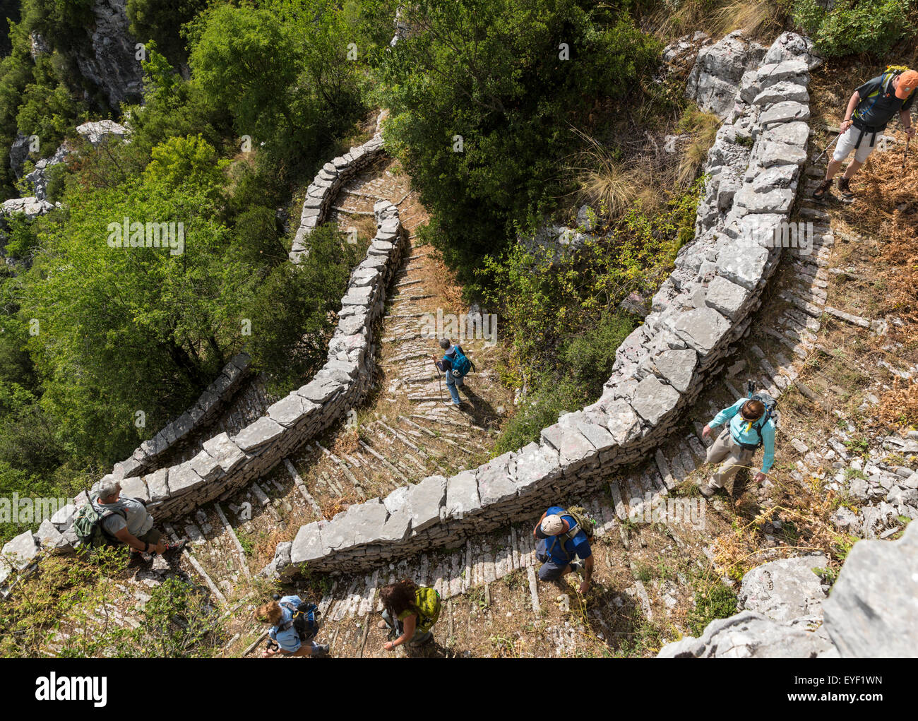 Hikers descend the Vradeto Stairs, a 17th Century stone mule trail in the Zagoria region of Greece. - Stock Image