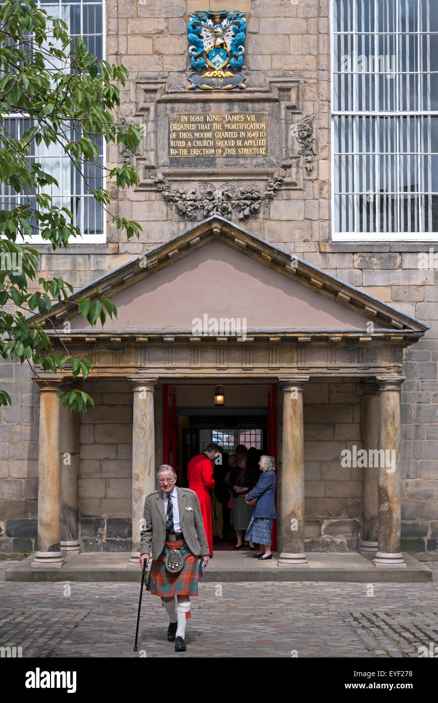 A parishioner dressed in a kilt leaving the Canongate Kirk in Edinburgh after the Sunday morning service. - Stock Image