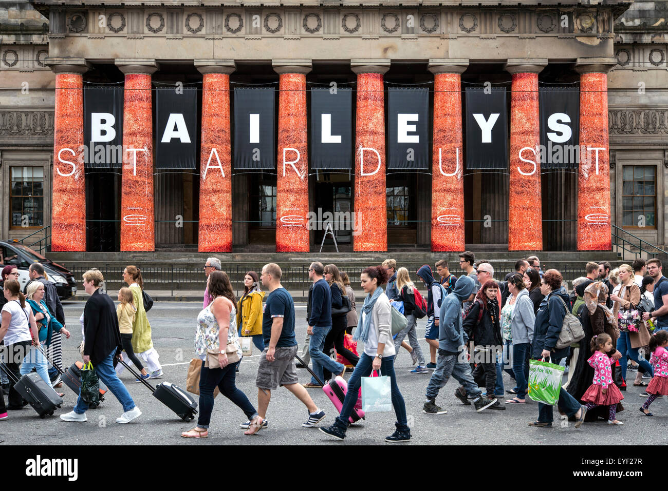 Pedestrians cross Princes Street in front of the Royal Scottish Academy which is hosting a David Bailey exhibition. - Stock Image