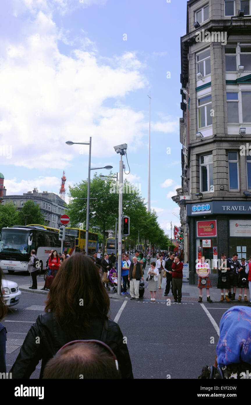 Pedestrians cross the road to walk towards The Spire of Dublin on O'Connell Street in Dublin, Ireland. - Stock Image