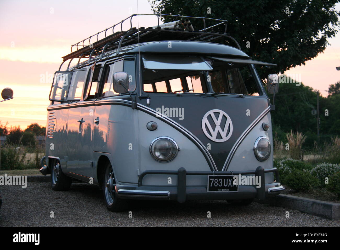 A TWO-TONE GREY RETRO MODIFIED 1962 VOLKSWAGEN VW CAMPER BUS TAKEN AT DUSK WITH THE SUNSET BEHIND THE VEHICLE - Stock Image