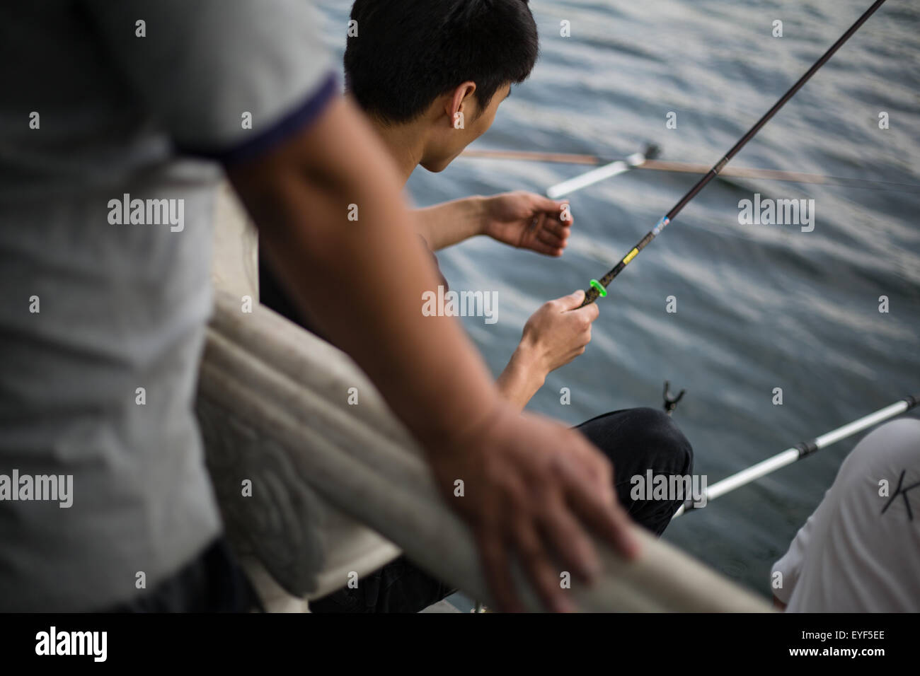Men fishing in HouHai Lake, in Beijing, China. - Stock Image