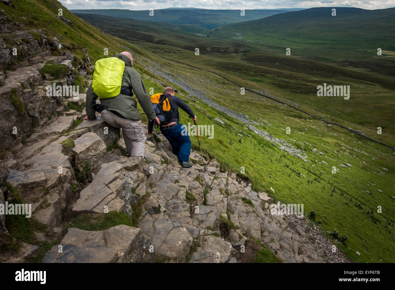 Two people descending carefully off the steep, rocky section of Pen-y-ghent in the Yorkshire Dales, part of the - Stock Image