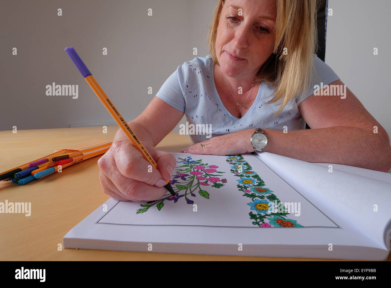 An adult woman colouring in a vintage design colouring in book, a new trend in relaxation for adults - Stock Image