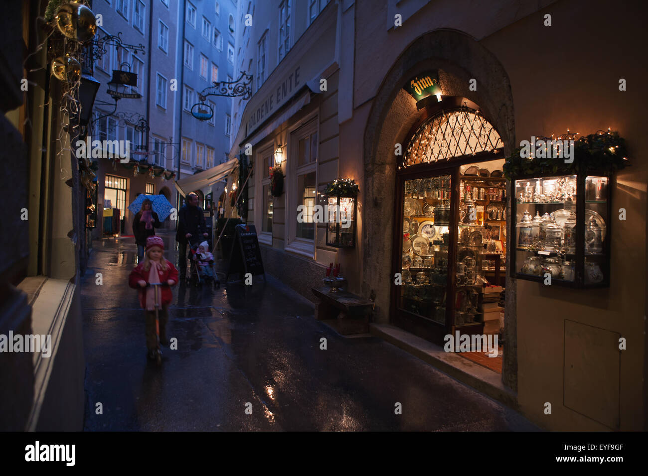 A family strolls past an antique shop in the pedestrianised streets of the old city on a rainy day; Salzburg, Austria Stock Photo