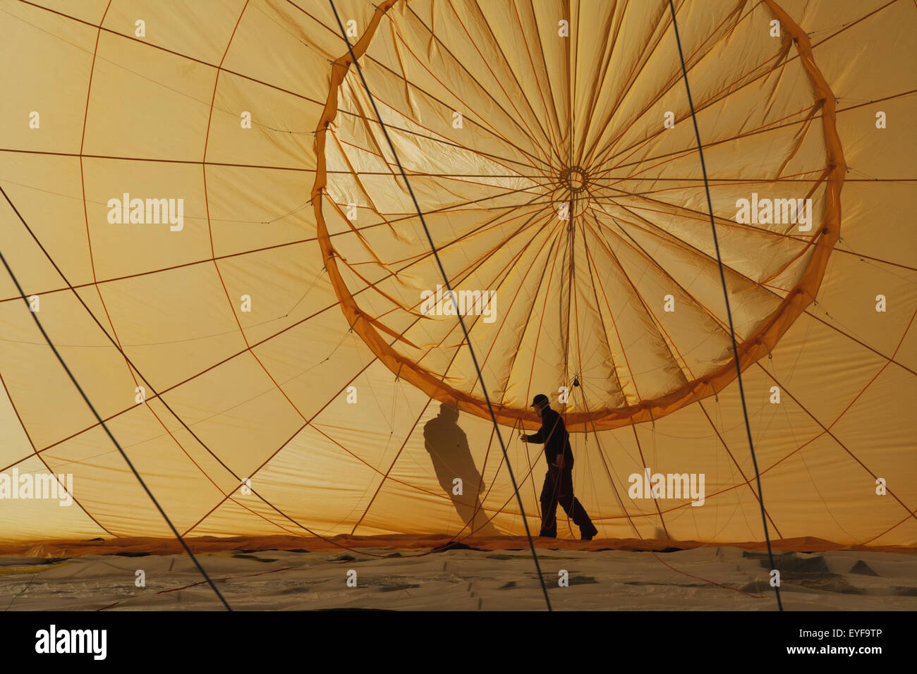 A man checks ropes inside a hot air balloon as it lies on the ground being inflated; Filzmoos, Austria - Stock Image