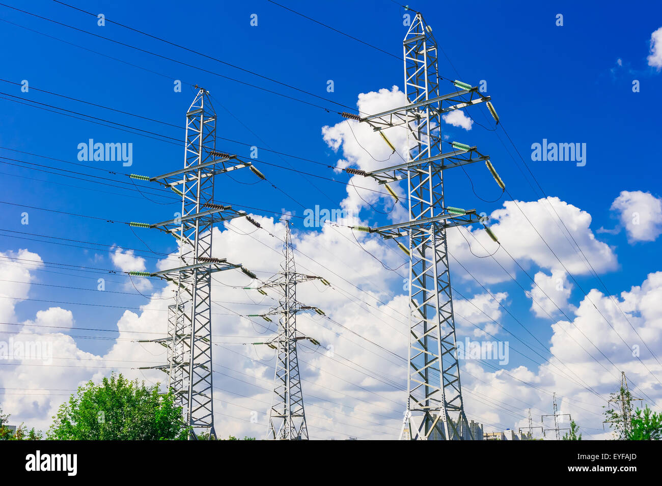 Power line towers on blue sky background - Stock Image