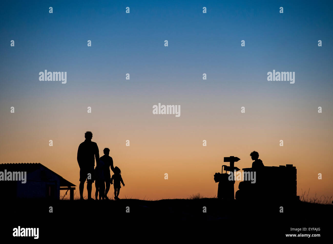 Silhouette of a family standing and watching the sunset; Cabo Polonio, Uruguay - Stock Image