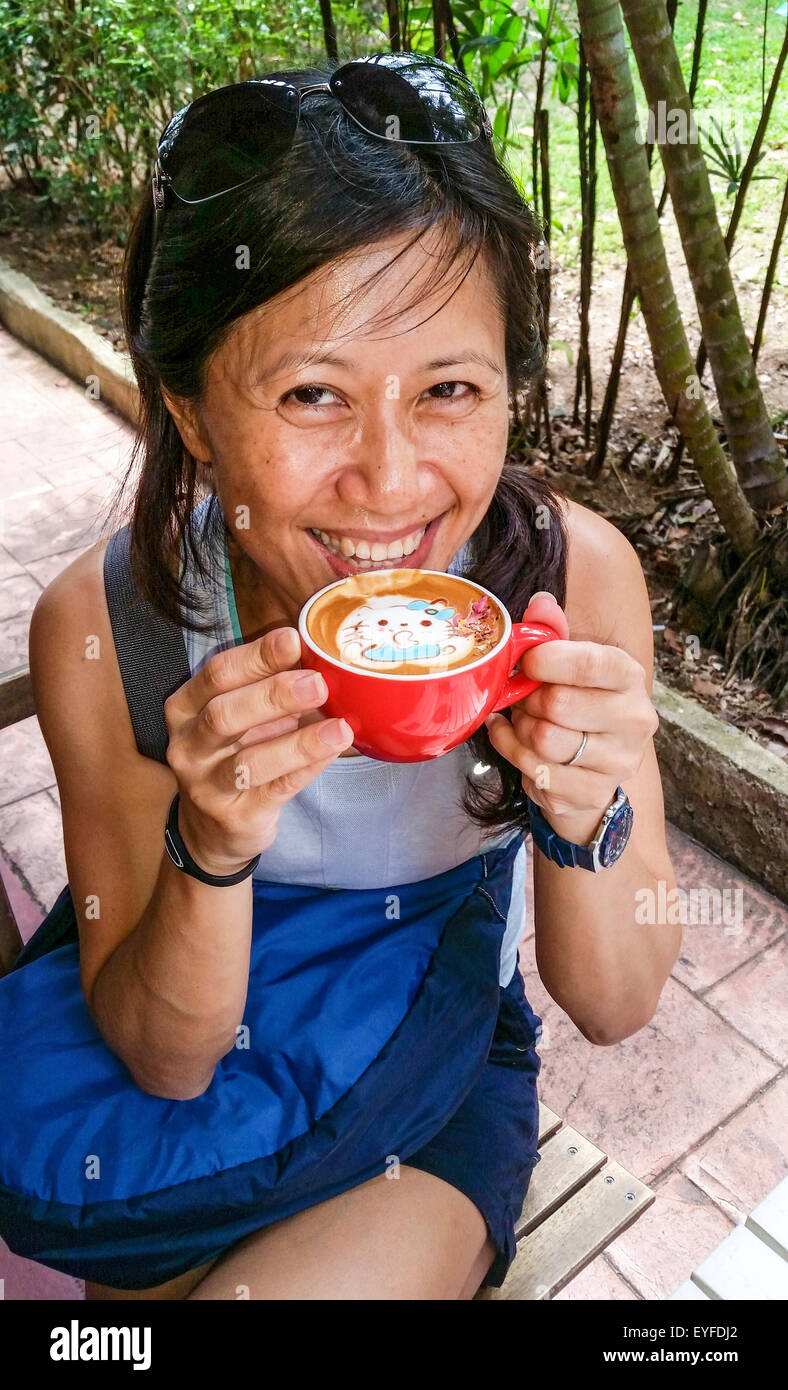 Fancy latte with a Hello Kitty design being enjoyed by a local Singapore woman at Chock Full of Beans, a coffee - Stock Image