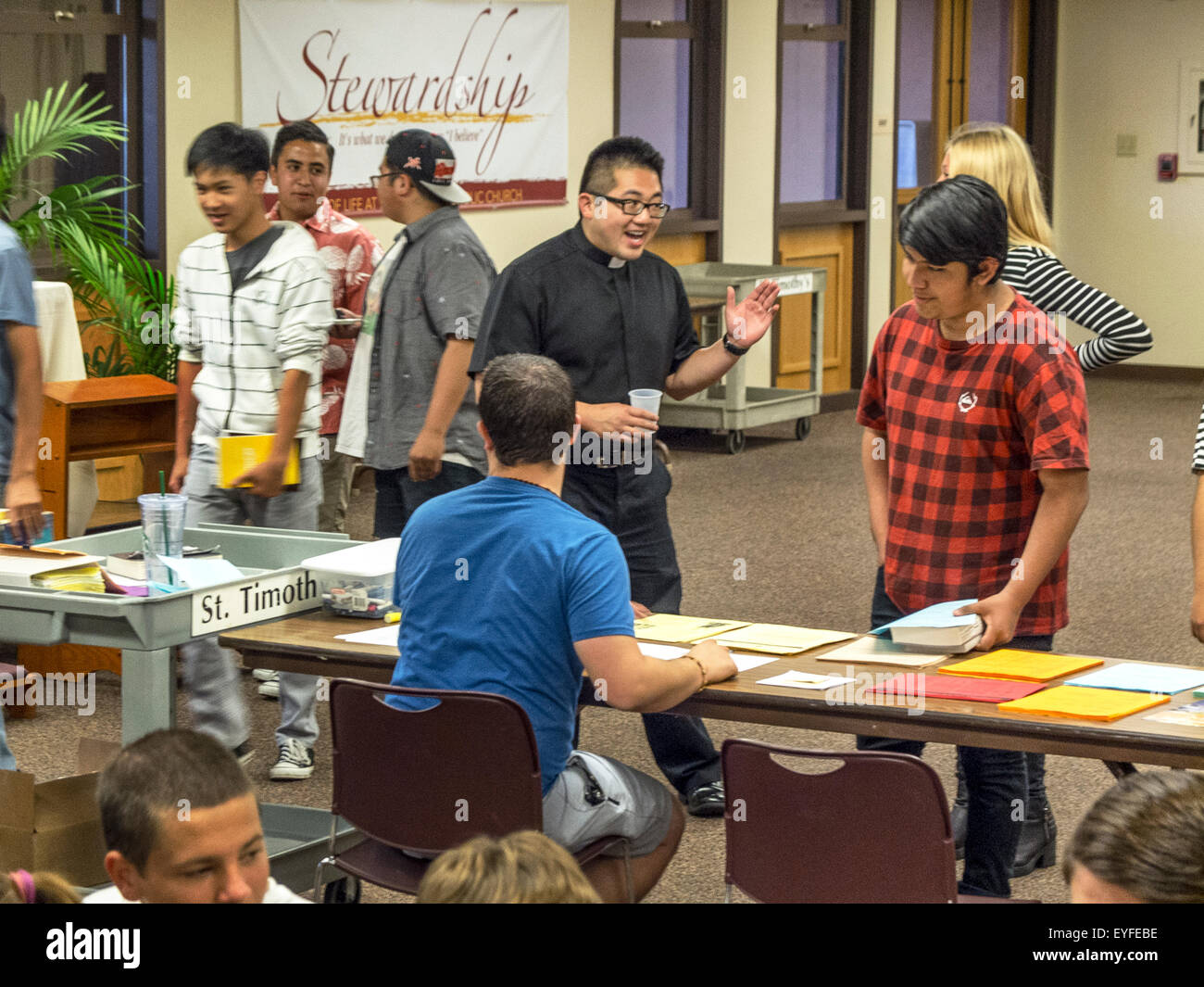 A Vietnamese American priest talks encouragingly to a teenager at a confirmation preparation class in the parish - Stock Image