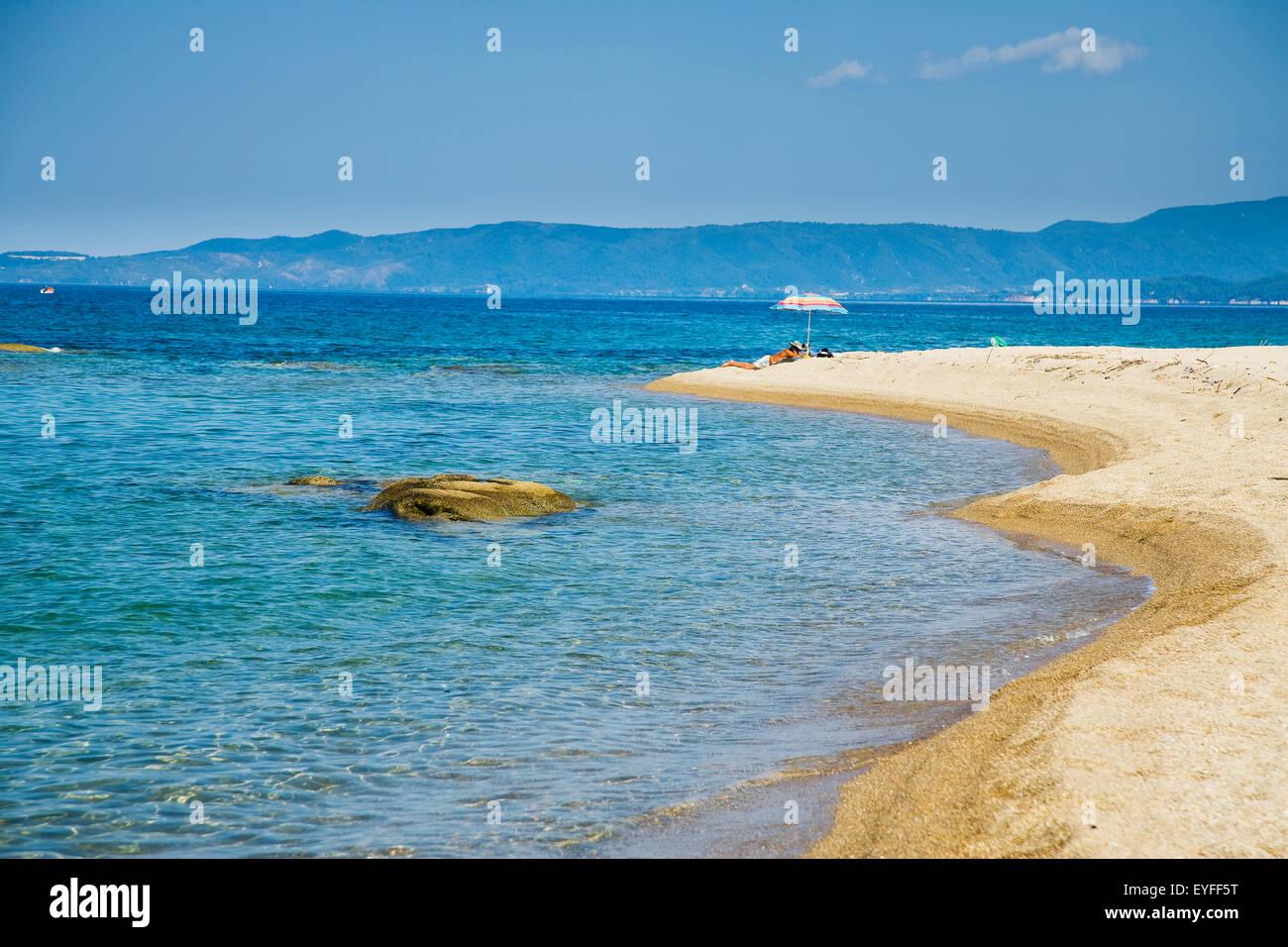 Greece, Halkidiki, Solitary sunbather lying under a beach parasol; Ierissos - Stock Image