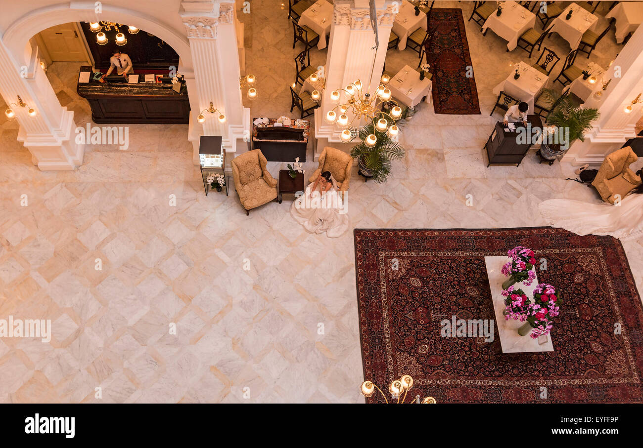Bride-to-be sits in the Raffles Hotel lobby, waiting to have pictures taken. - Stock Image