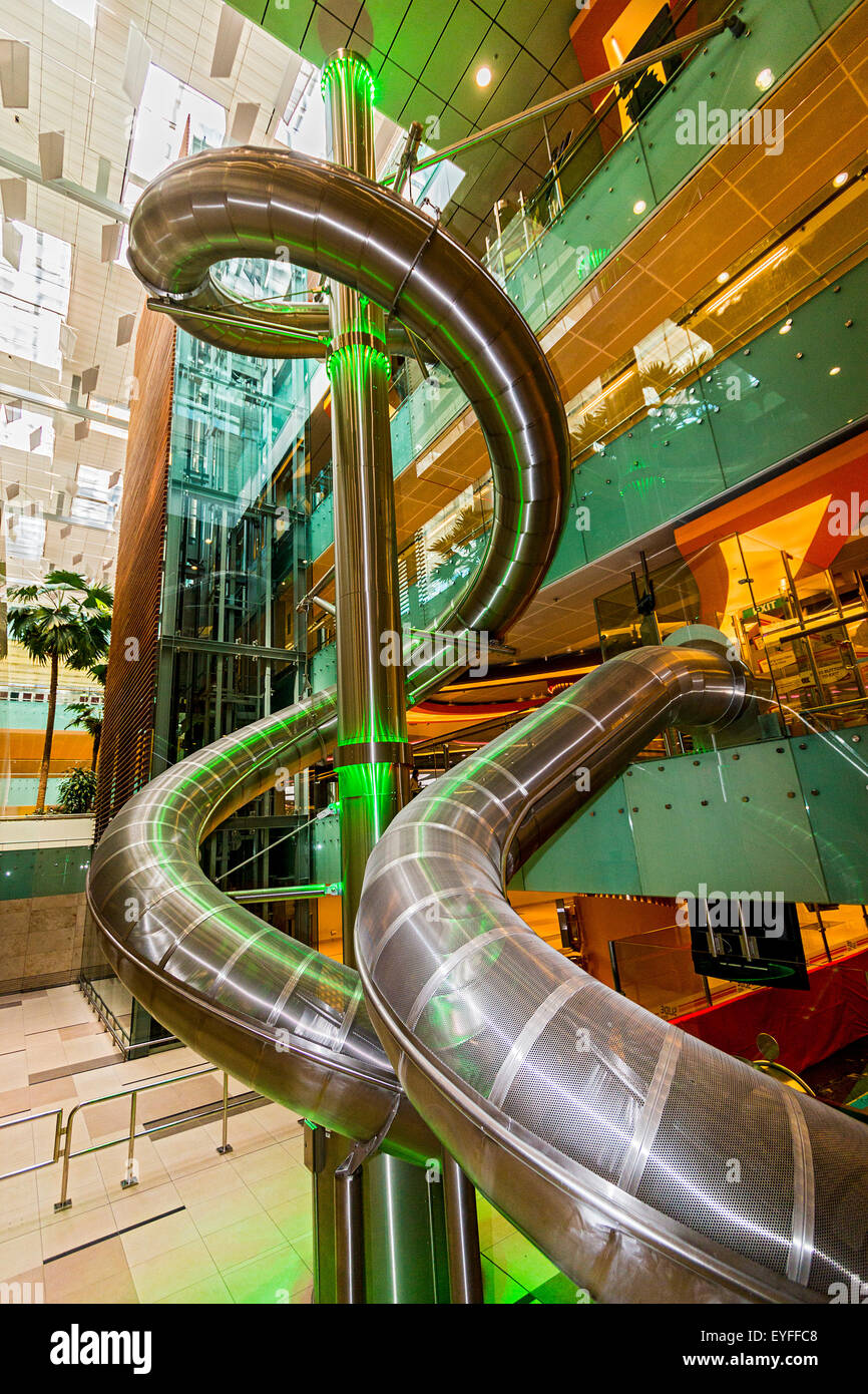 Four-story slide in the public (non security) area of Changi, Singapore's international airport. - Stock Image