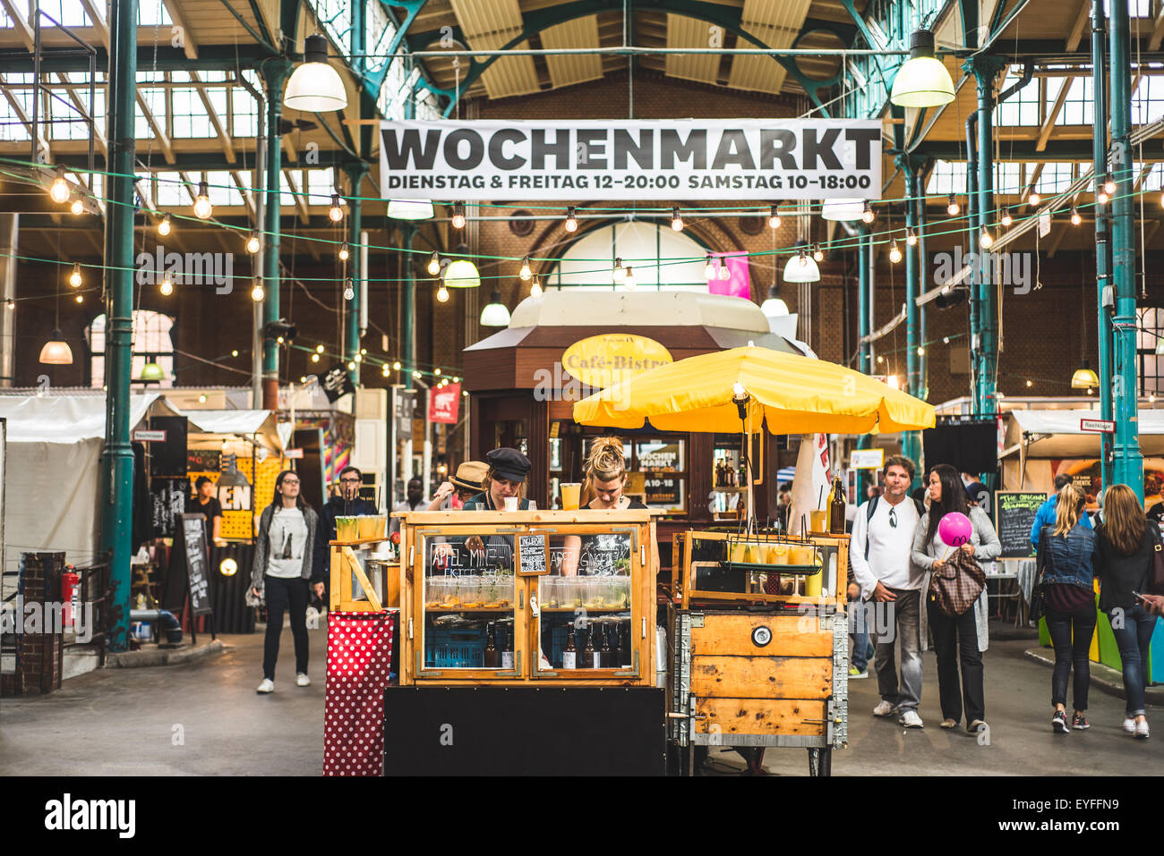 People gather in Markthalle Neun to enjoy organic street food. - Stock Image