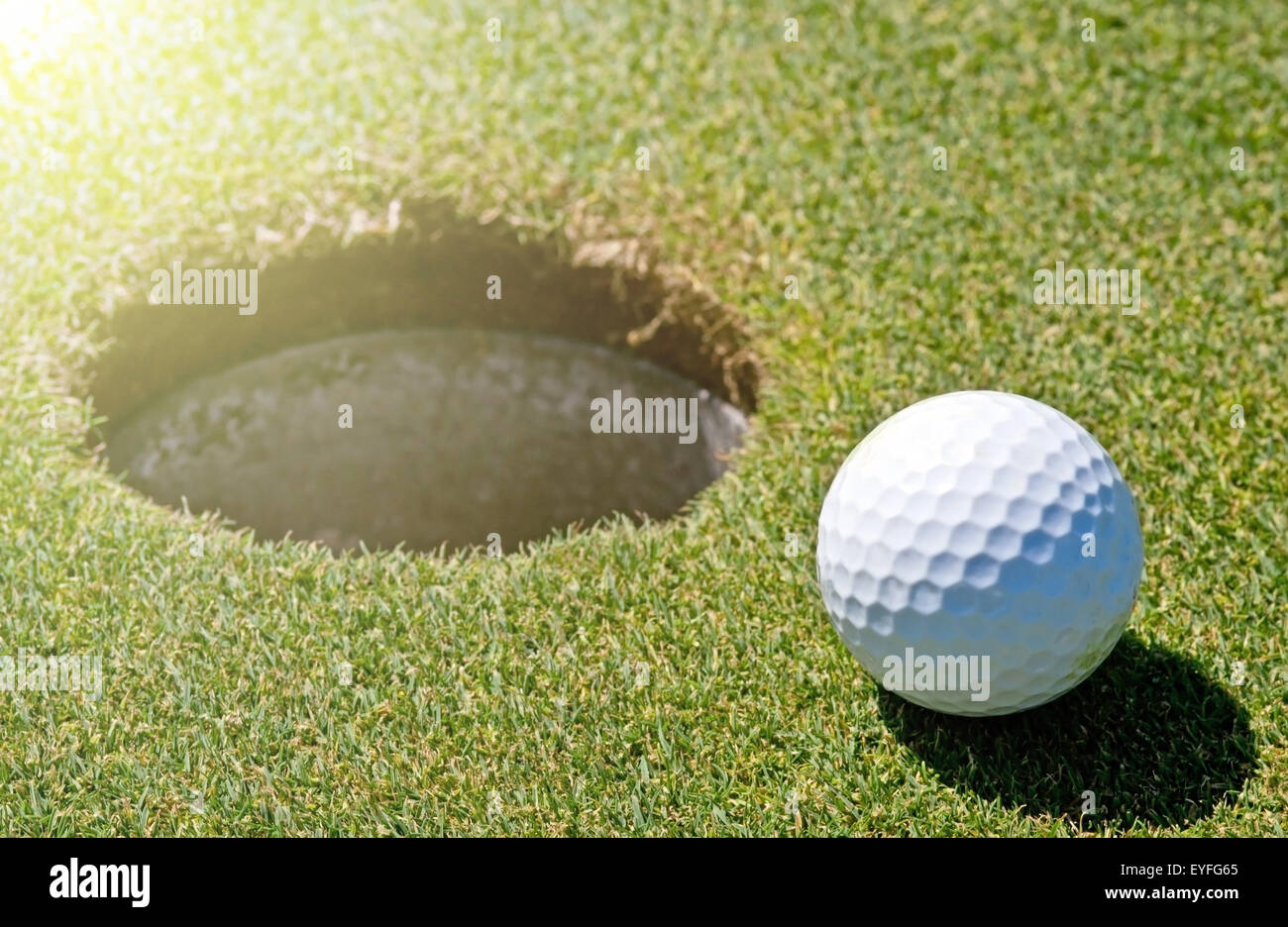 Golf ball next to a hole on a golf course - Stock Image