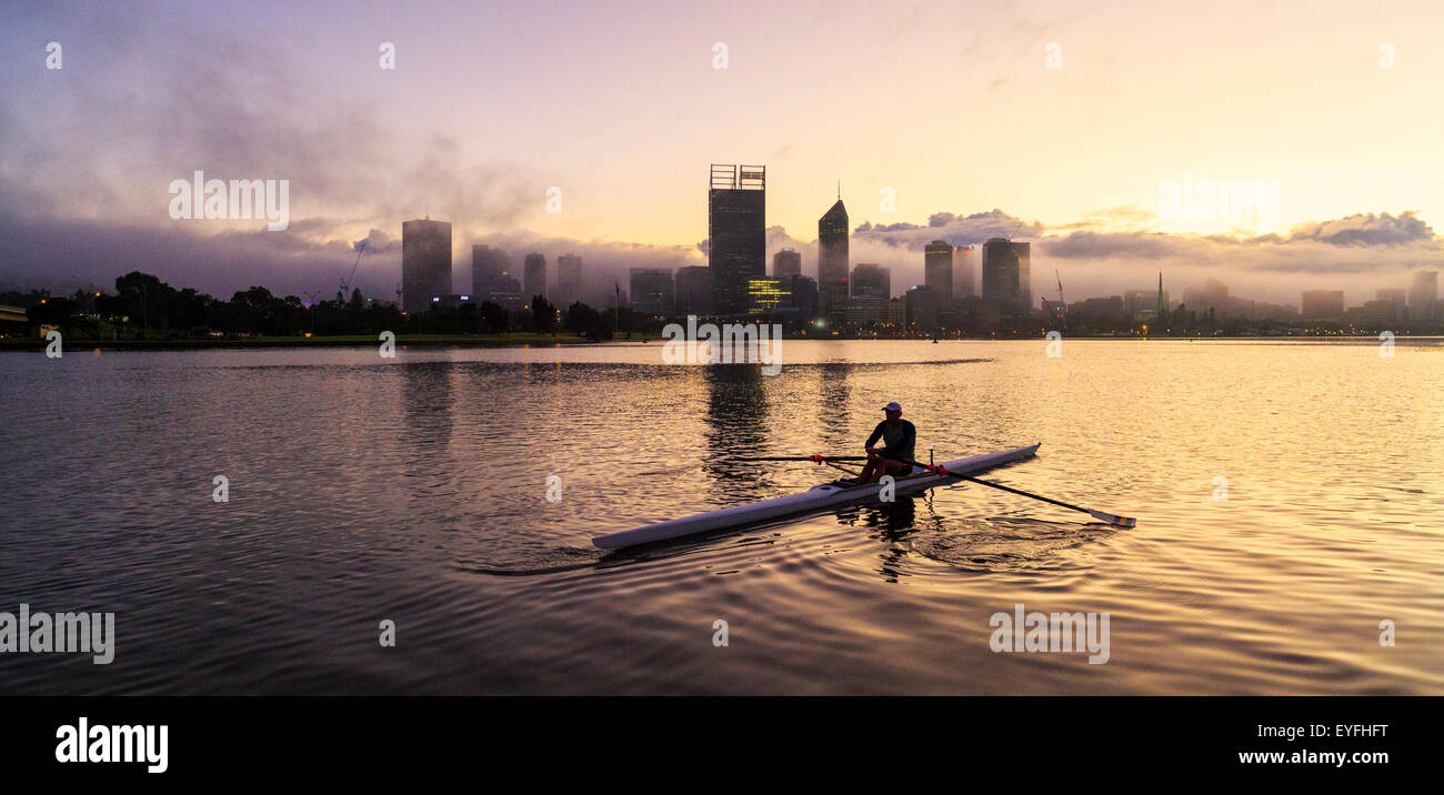 A man in a K1 racing kayak on the Swan River at sunrise. - Stock Image