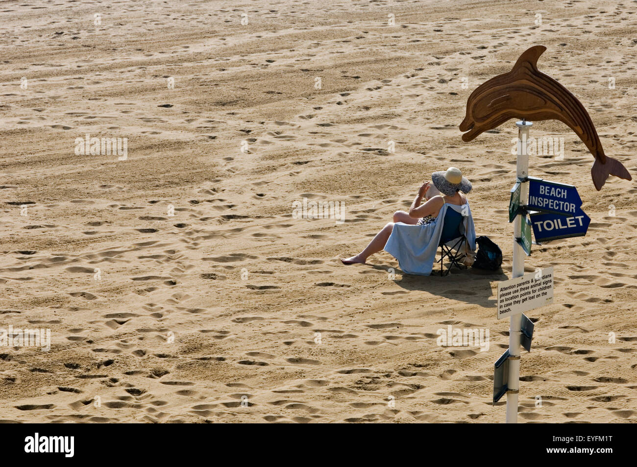 A lone woman sitting on the beach at Viking Bay; Broadstairs, Thanet, Kent, England - Stock Image