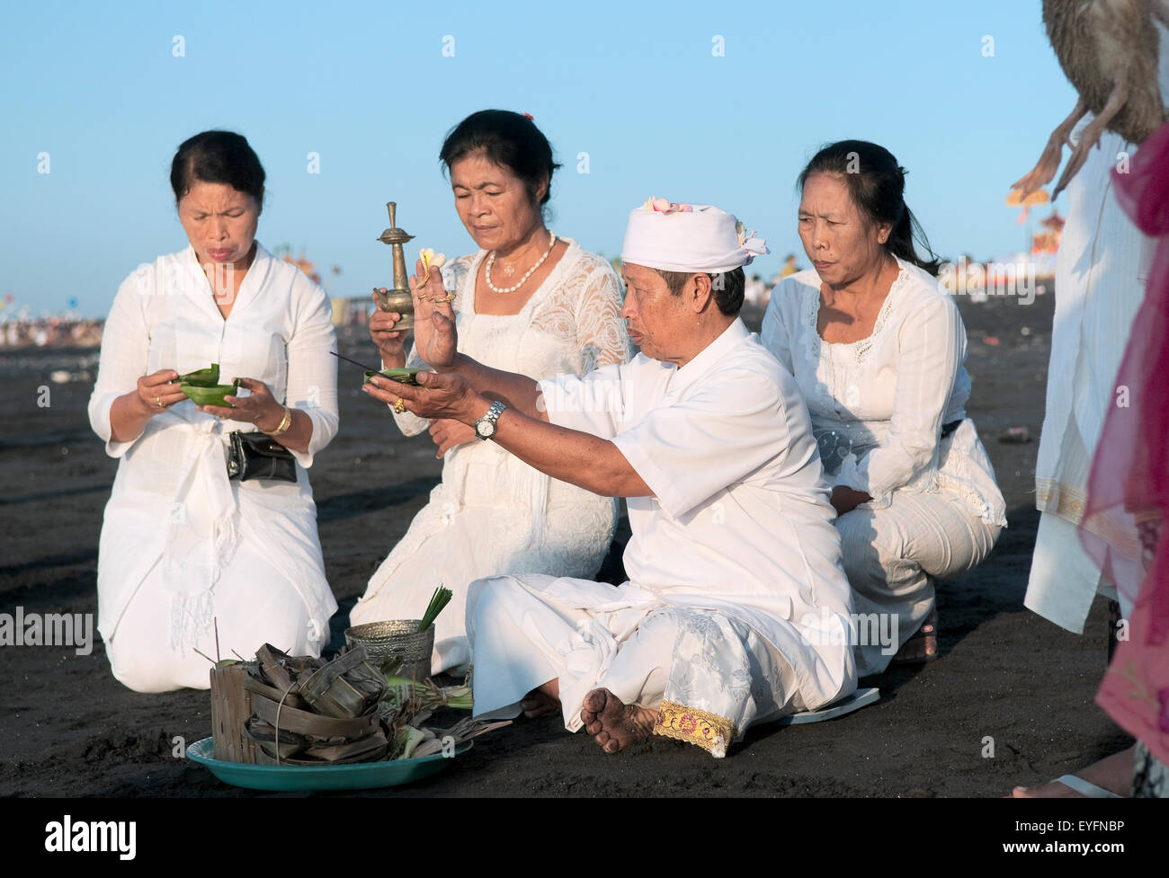 Family and priest making an offering at the Melasti Festival to honor the gods of the sea; Bali, Indonesia - Stock Image