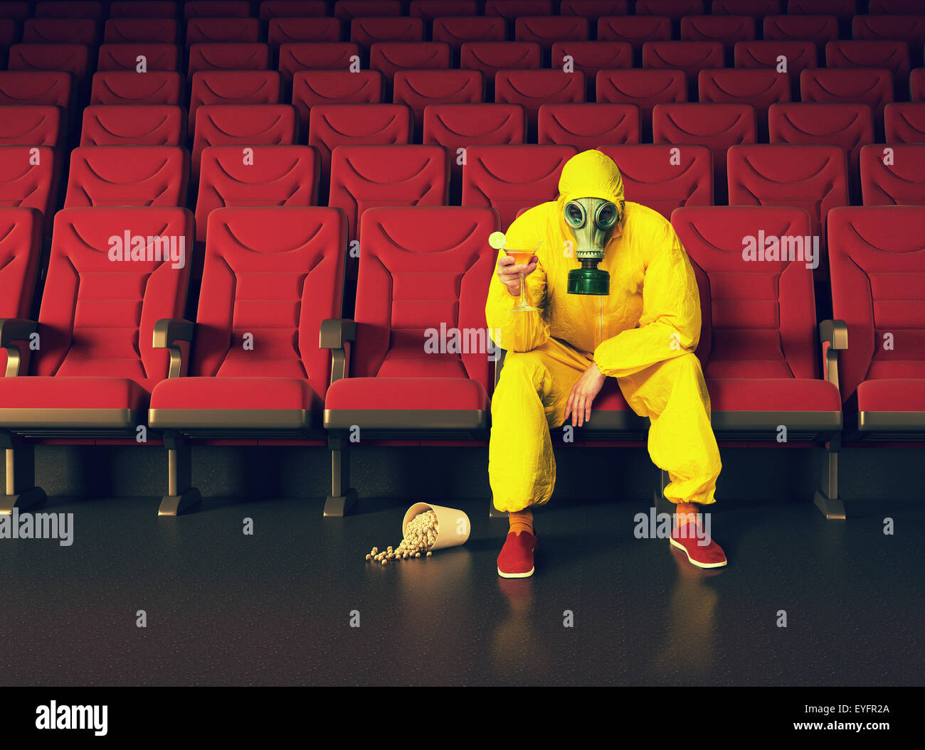 the man in a protective coverall  sitting in an empty theater - Stock Image