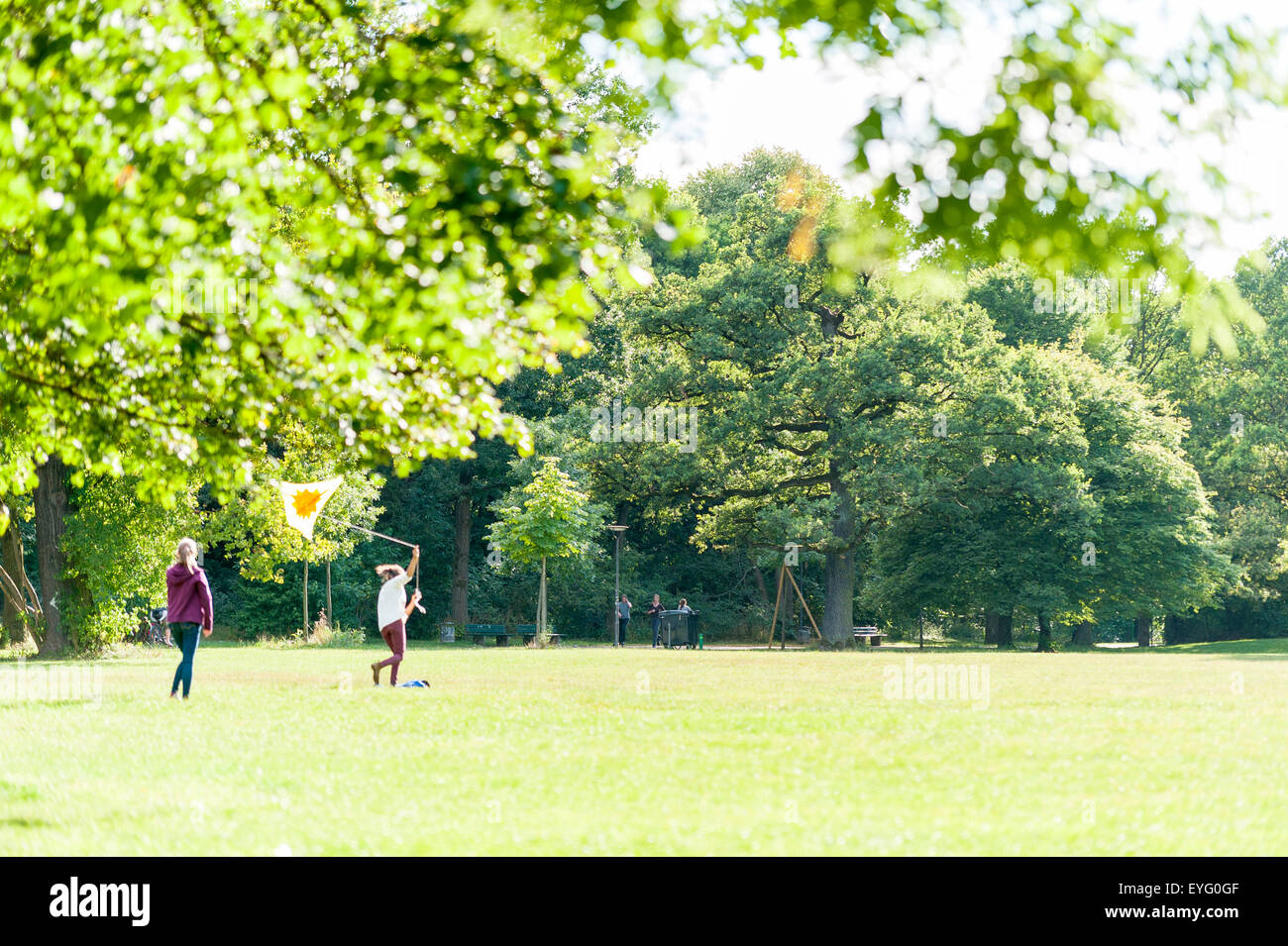 Girls fly a kite in the park - Stock Image