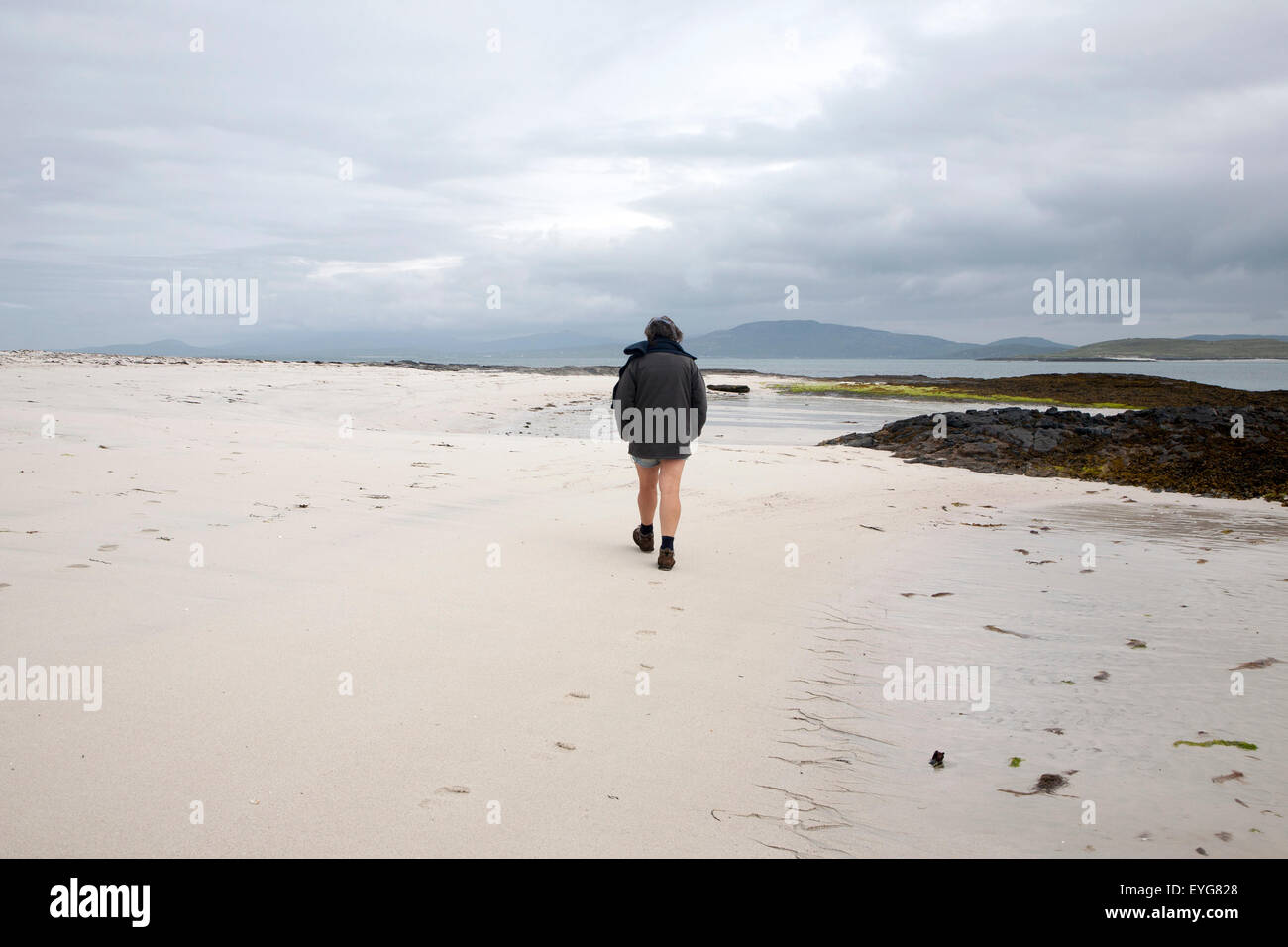 Woman walking overcast sky sandy beach Eoligarry, Barra, Outer Hebrides, Scotland, UK - Stock Image