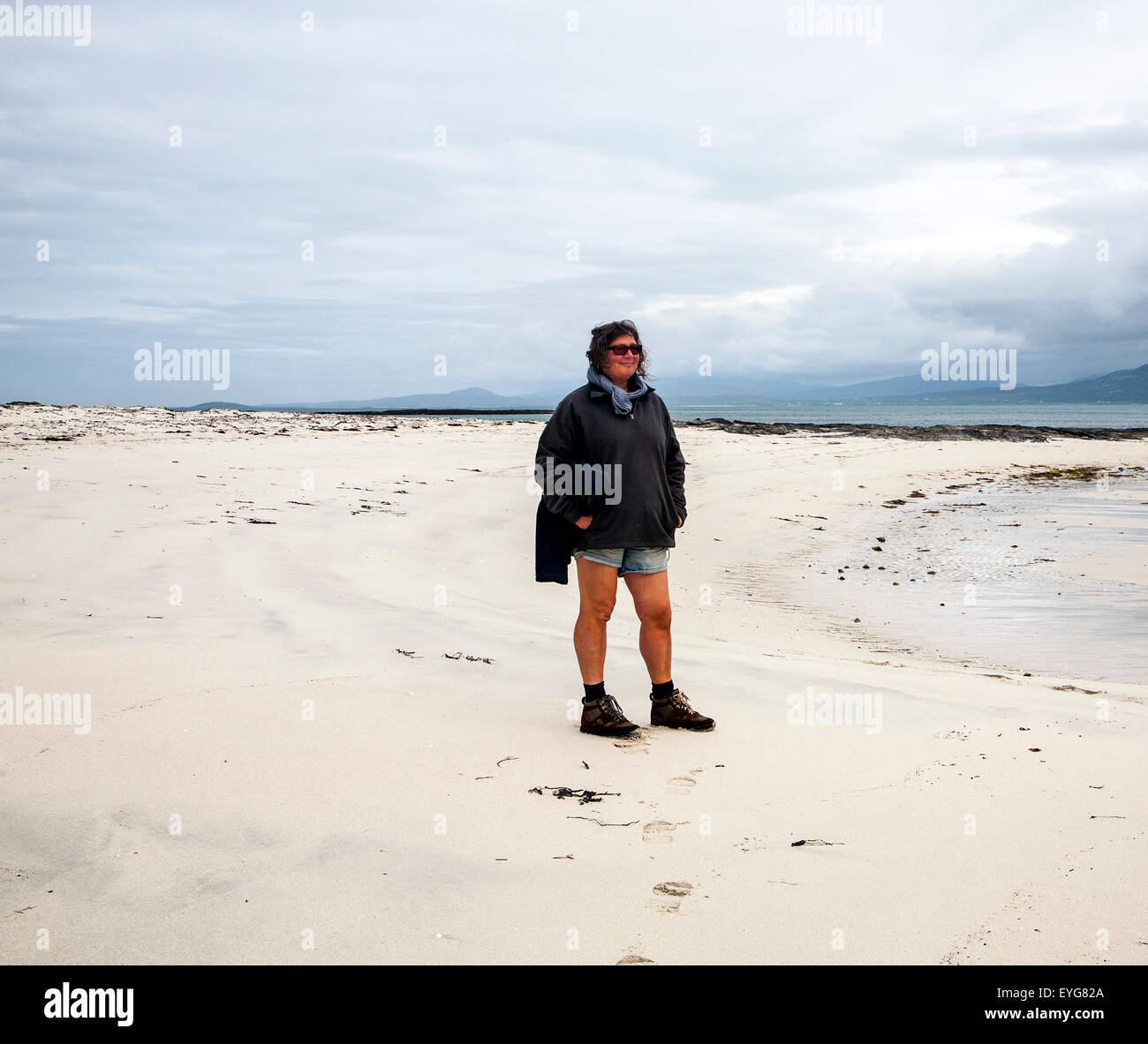 Woman standiing overcast sky sandy beach Eoligarry, Barra, Outer Hebrides, Scotland, UK - Stock Image