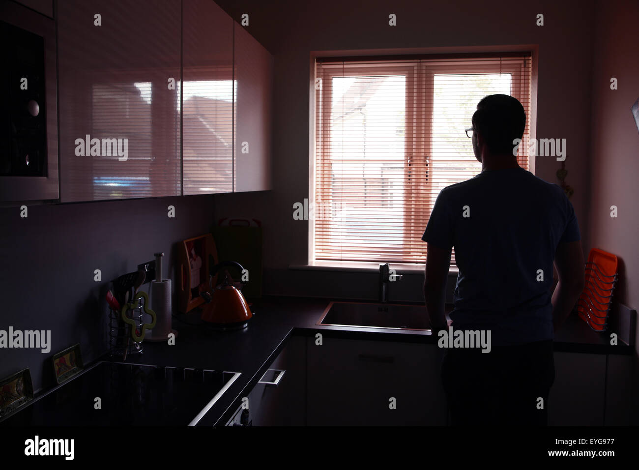 Young man in a kitchen looking out through a window blind. Landscape shape. - Stock Image