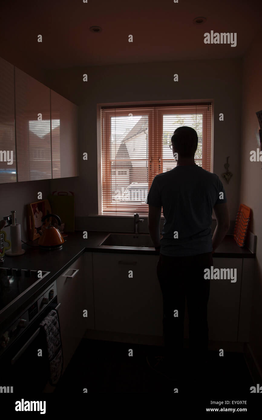 Young man in a kitchen looking out through a window blind. Portrait shape. - Stock Image