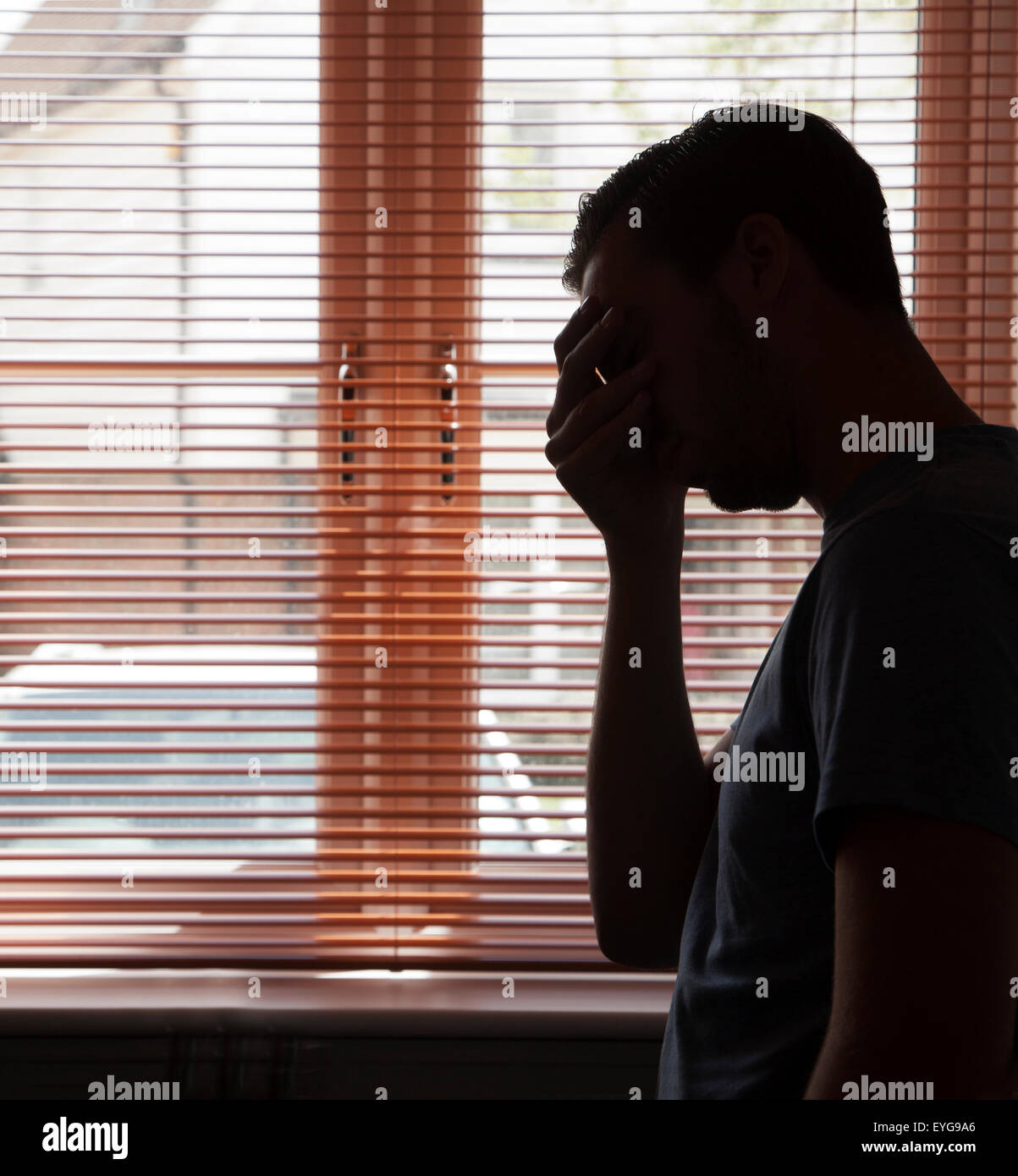 Silhouette of young male by a window. - Stock Image