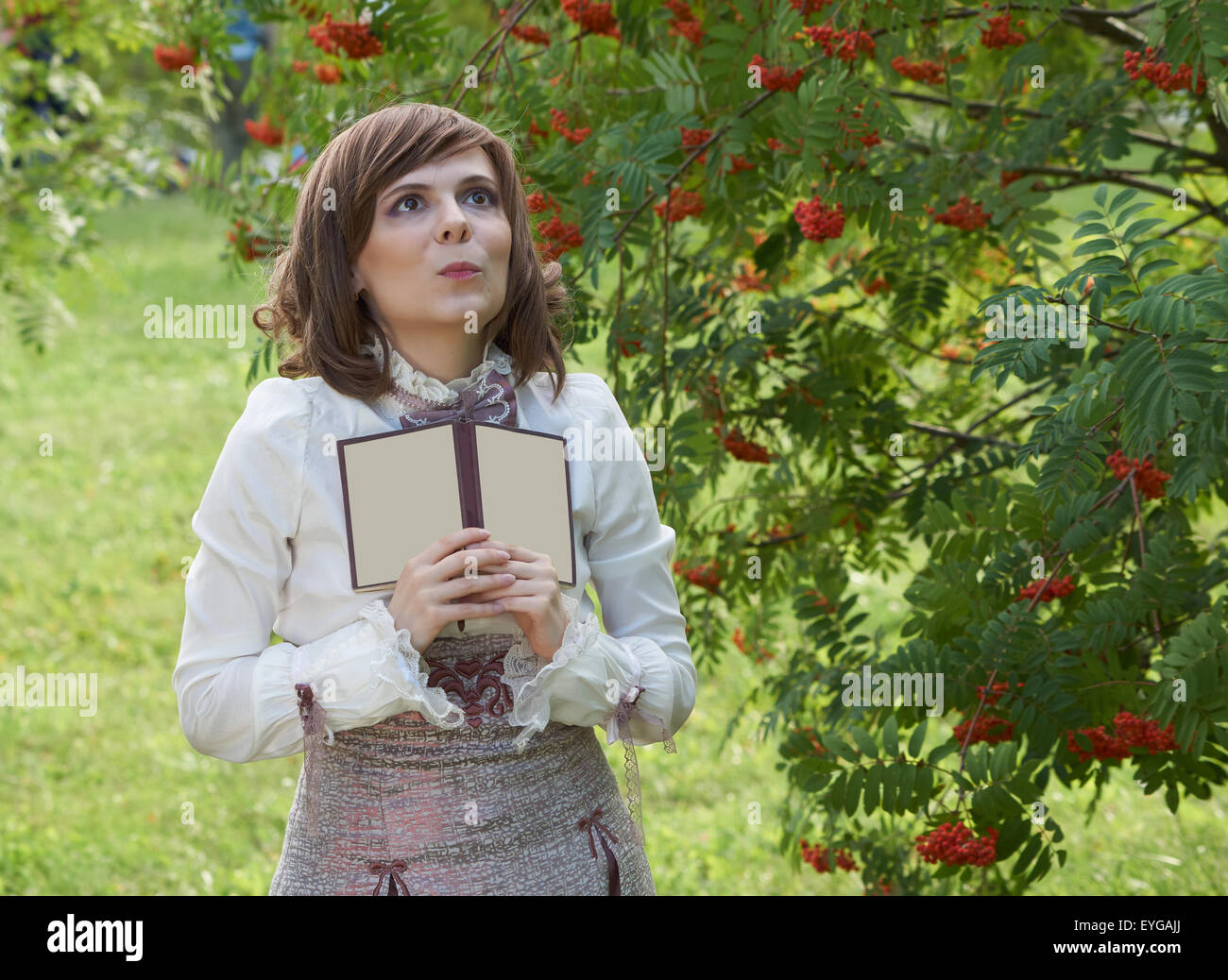 Delightful girl dressed in retro style dress with book stands in the bush of rowan - Stock Image