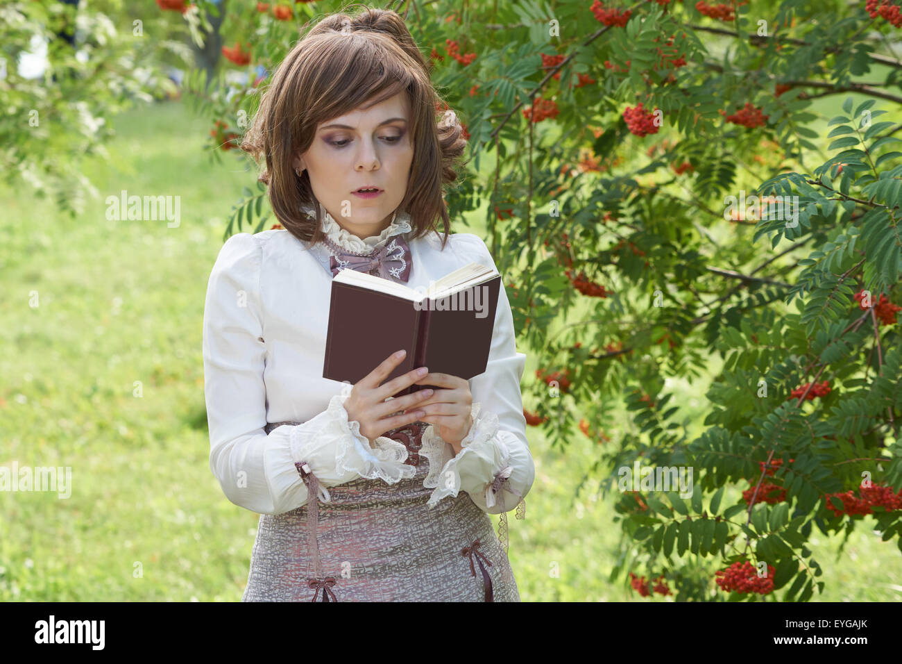 Girl dressed in retro style reads interesting book. Her mouth is slightly open - Stock Image