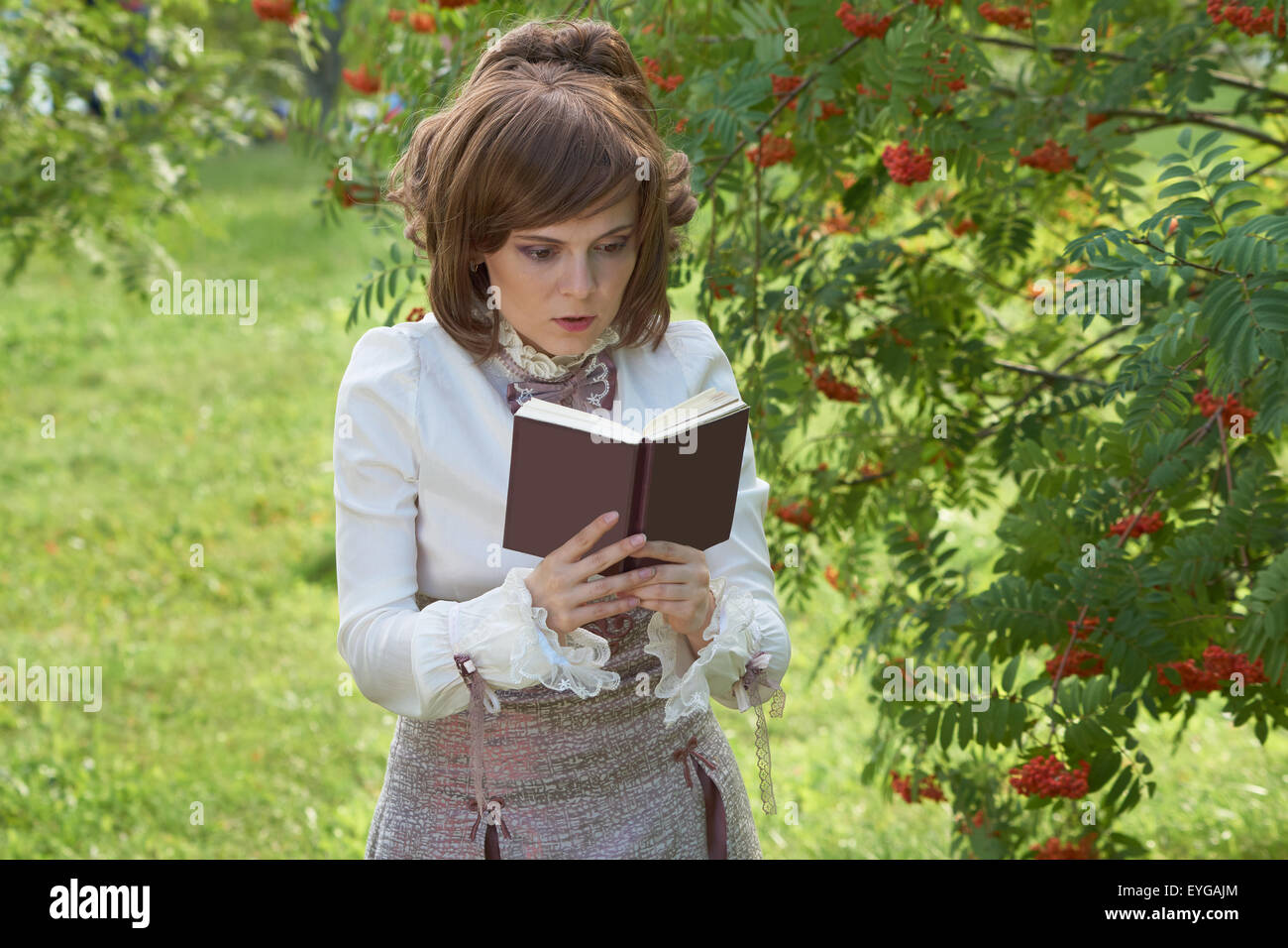 Beautiful girl reads book in the park - Stock Image