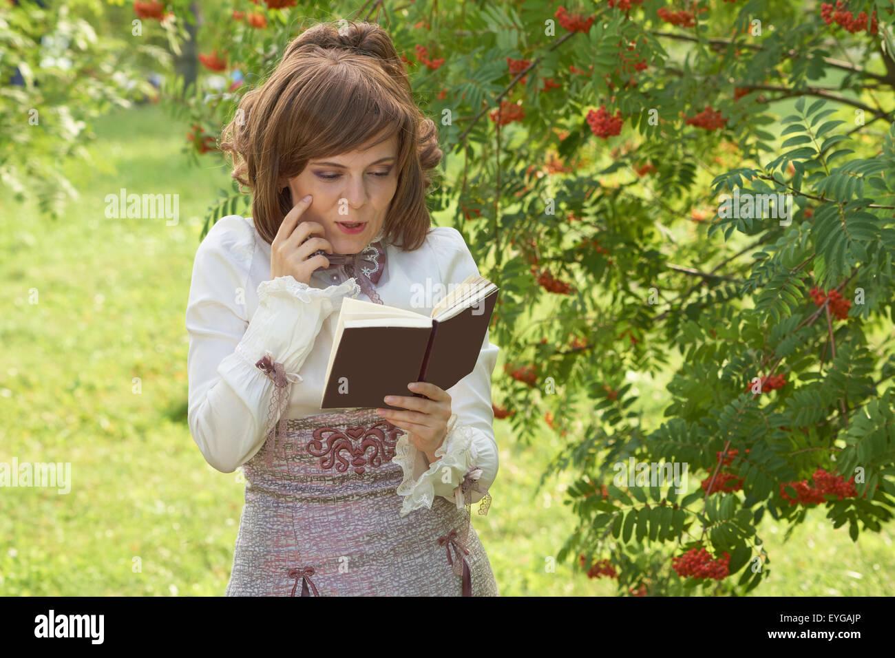 Smiling girl reads interesting book near rowan tree in summer - Stock Image