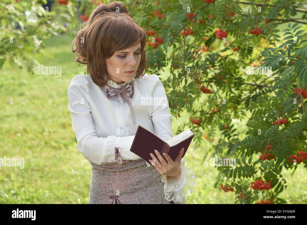 Beautiful girl found something interesting in the book while reading outdoors - Stock Image