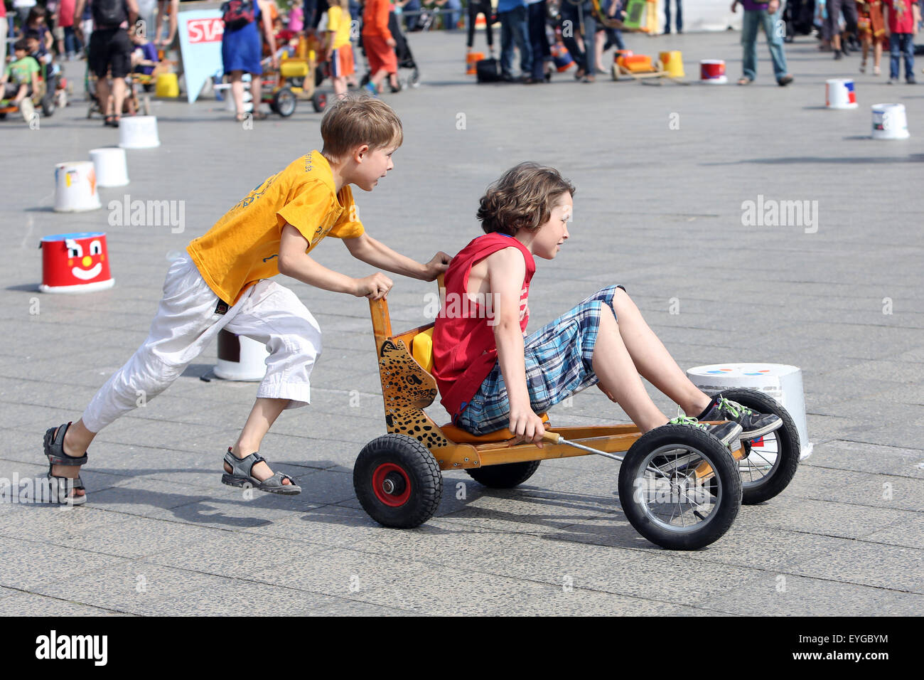 Berlin, Germany, boy pushes his big brother in the Kettcar at - Stock Image
