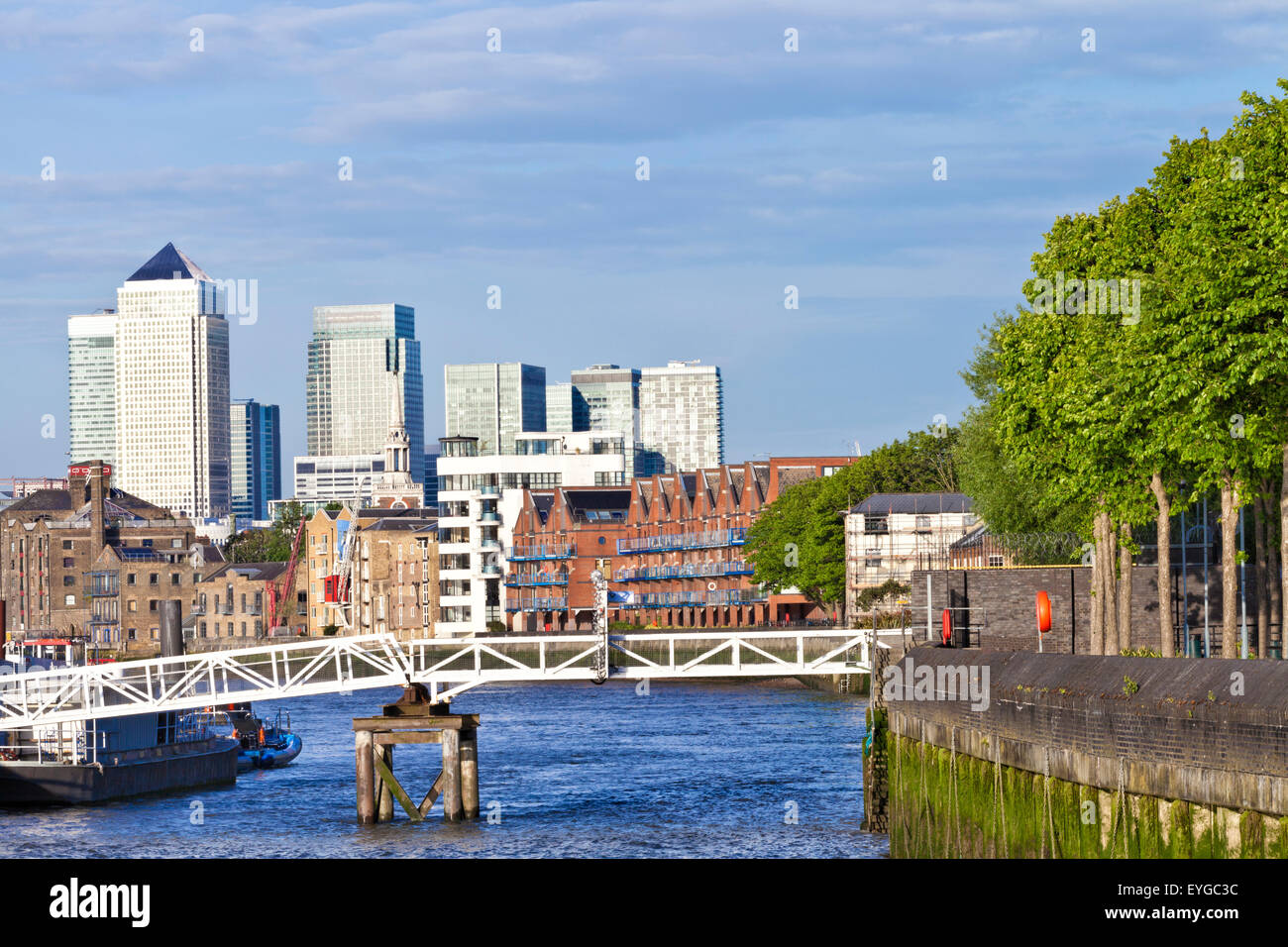 London Canary Wharf Docklands skyline view over Thames river along bankside with green trees, waterfront houses - Stock Image