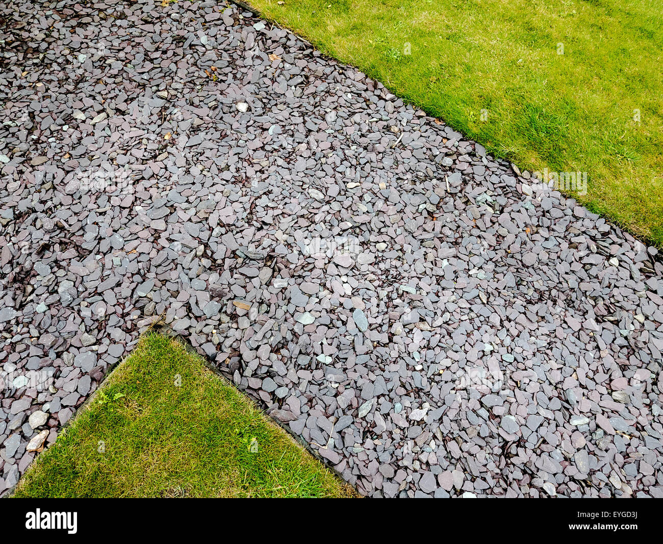 Path between lawns with shale surface showing contrasting surfaces - Stock Image