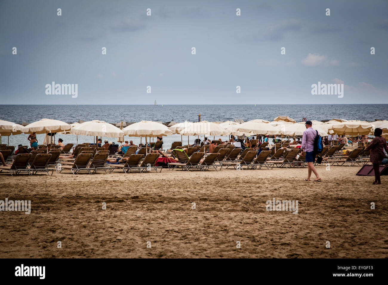 Sun loungers and straw shade umbrellas on a beach by the Mediterranean Sea Stock Photo